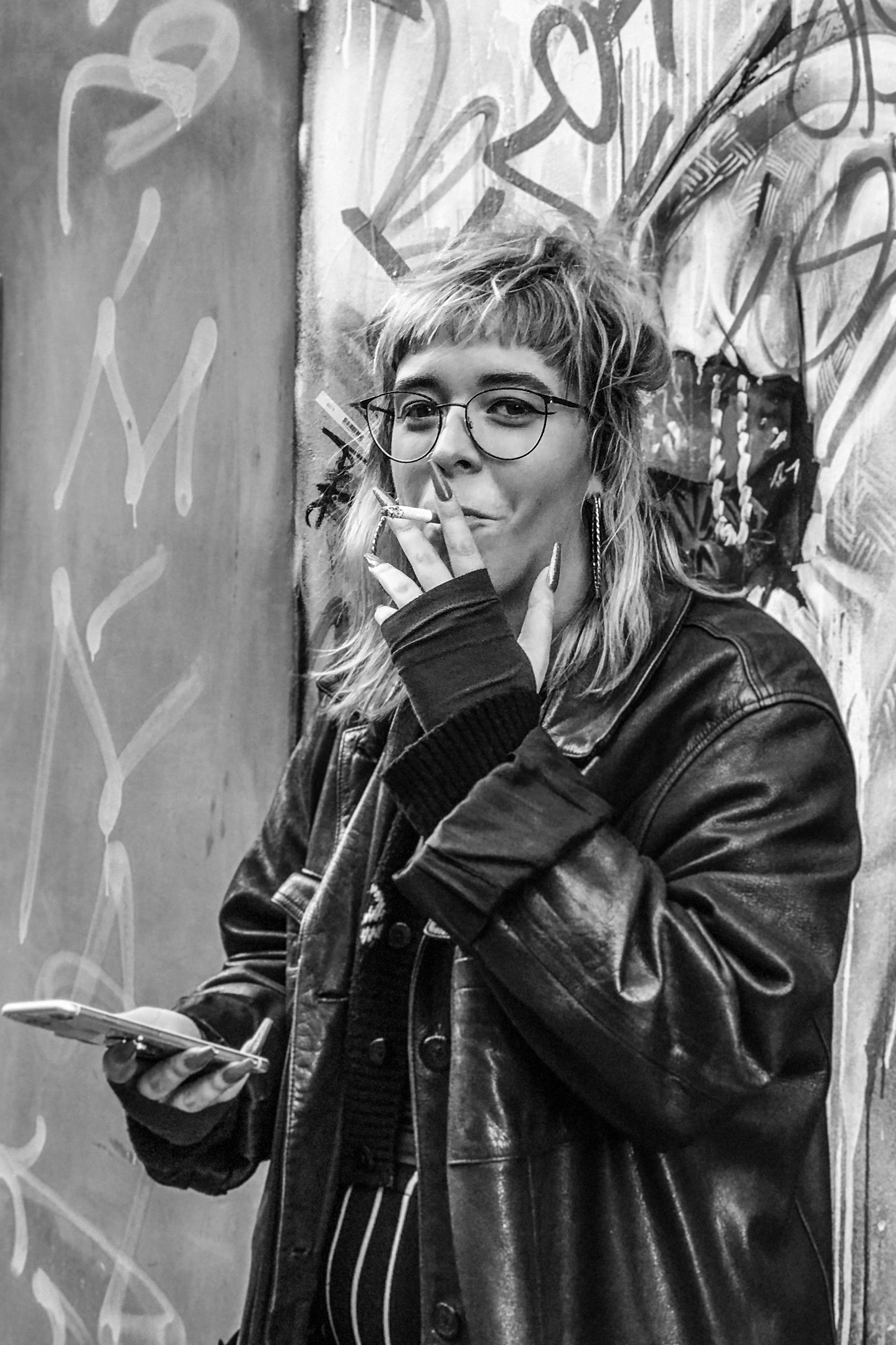 Black & White Portrait of a Stranger young woman with long nails smoking a cigarette looking directly at the camera