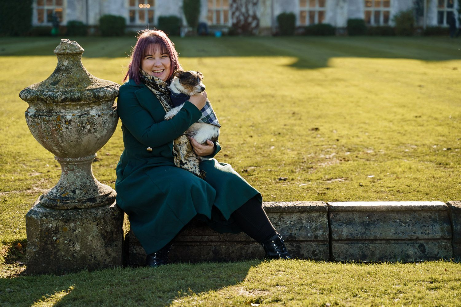 Dog-friendly wedding photographer Katherine hugs her Jack Russell in a walled garden. Top 10 dog-friendly wedding tips.