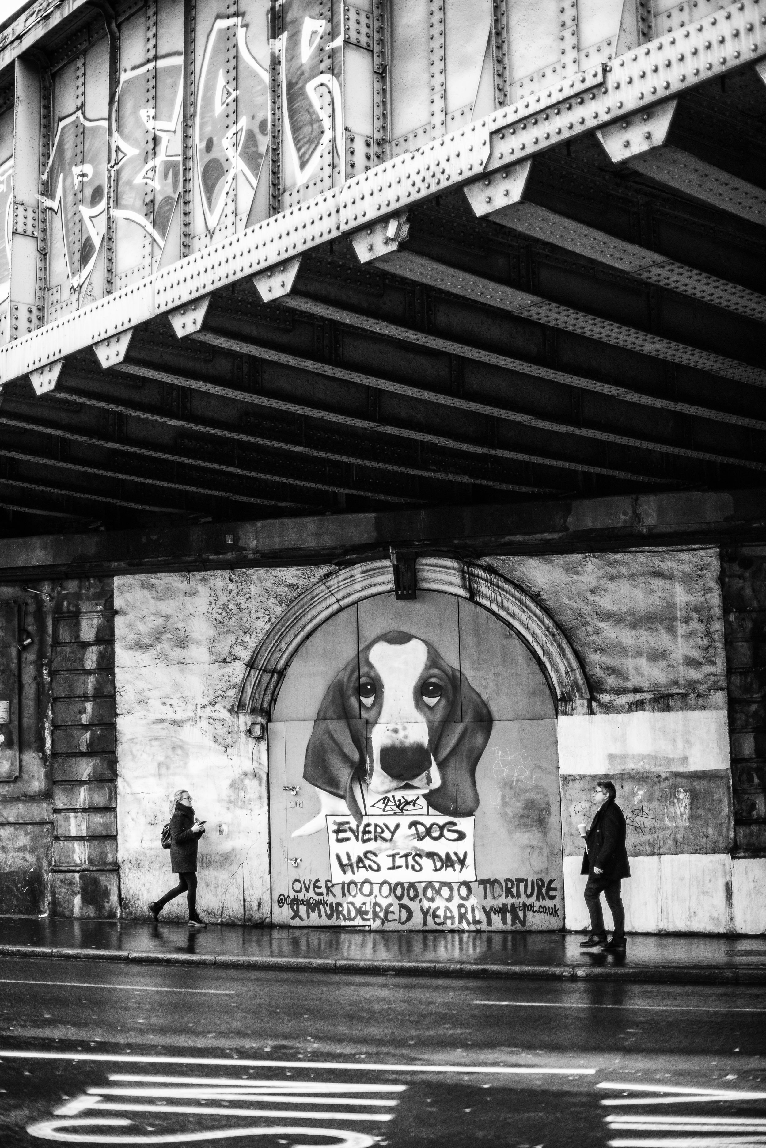 Grafitti under a bridge in London of a beagle with two people approaching