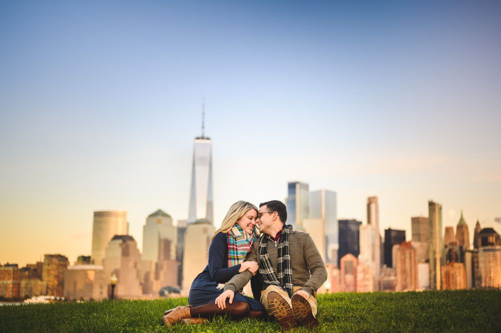 engaged couple sitting on hill smiling at each other at liberty state park