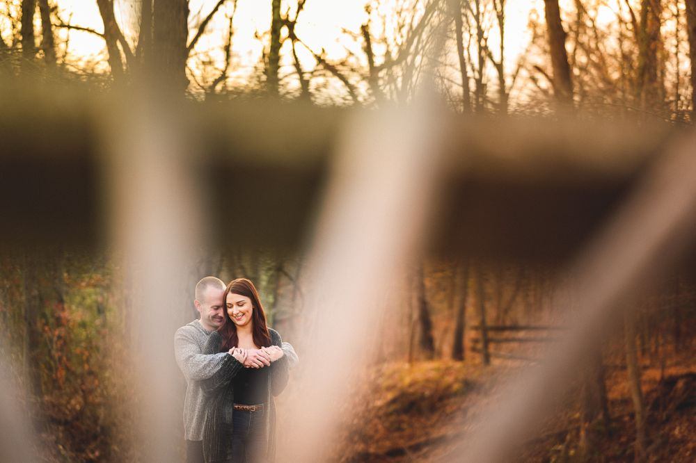 engaged couple holding each other and laughing at allaire state park