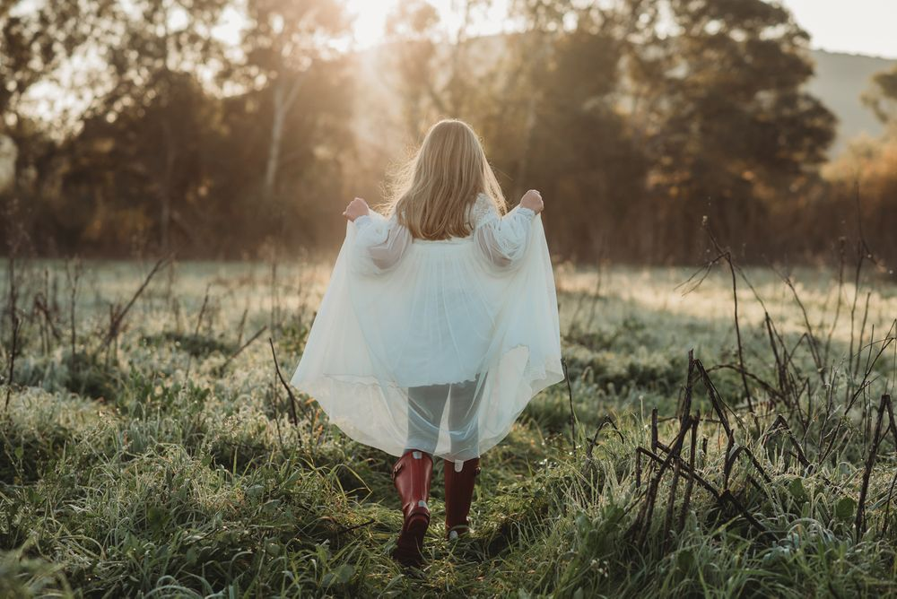 a girl in a communion dress and wellies running