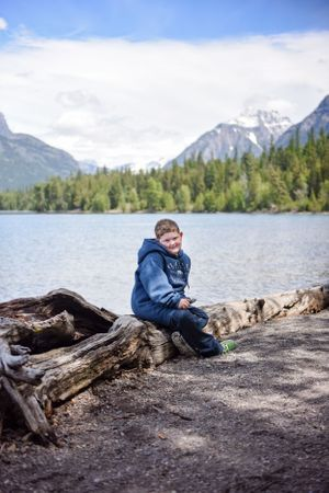 Grant relaxing with McDonald Lake and Glacier mountains behind him in Glacier National Park!