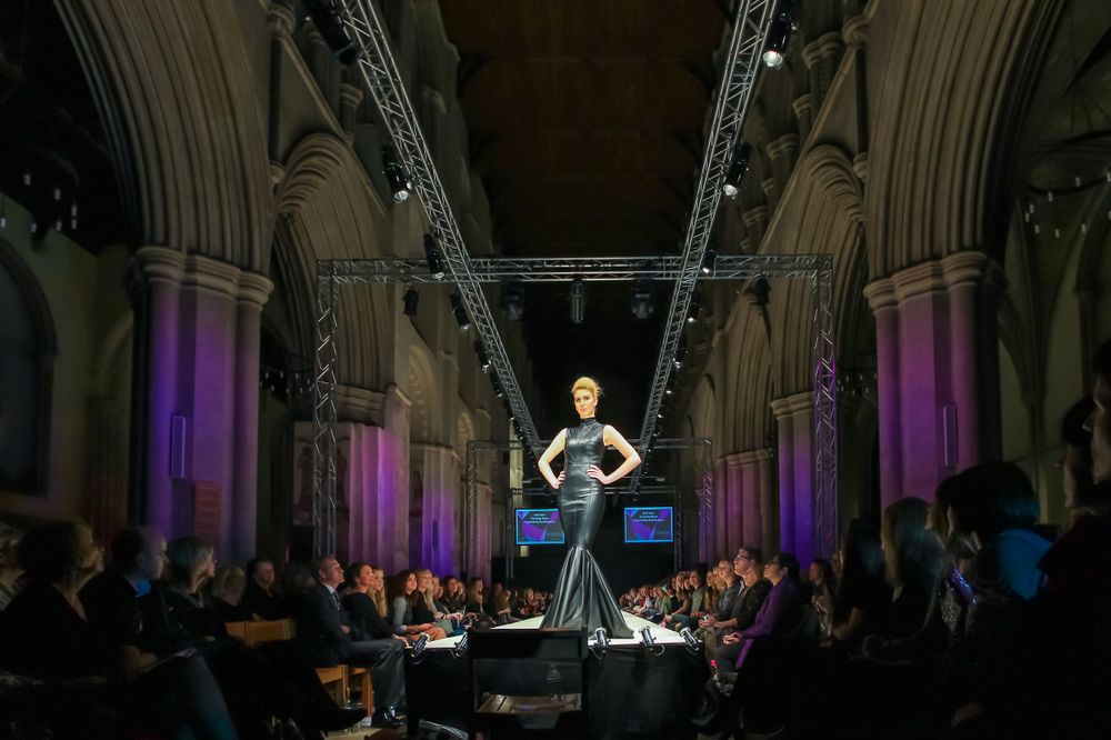A female model from Oaklands College stands at the end of St Albans Fashion Show catwalk in St Albans Abbey Cathedral