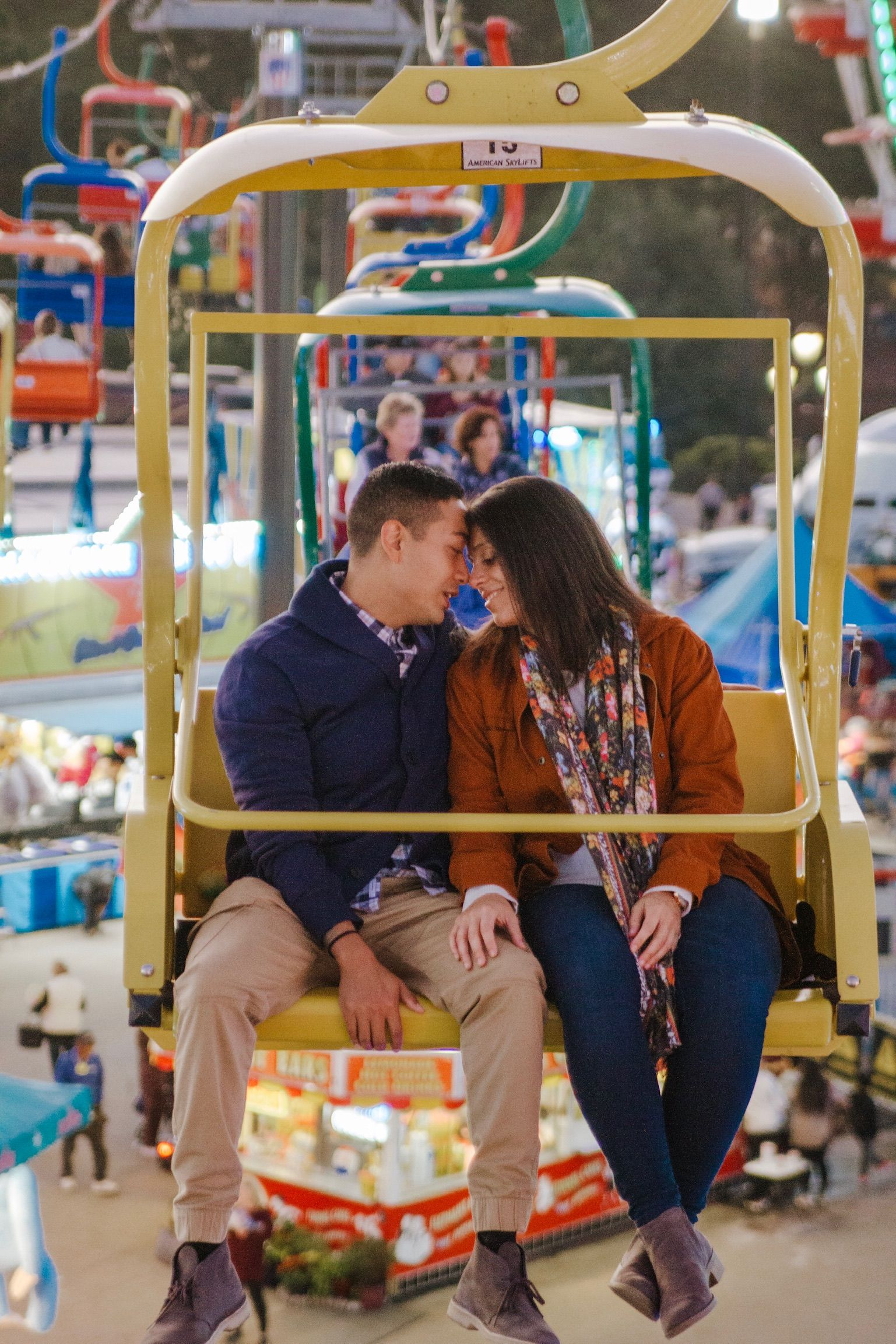 couple cuddling on an yellow skii lift chair at the state fair in north carolina