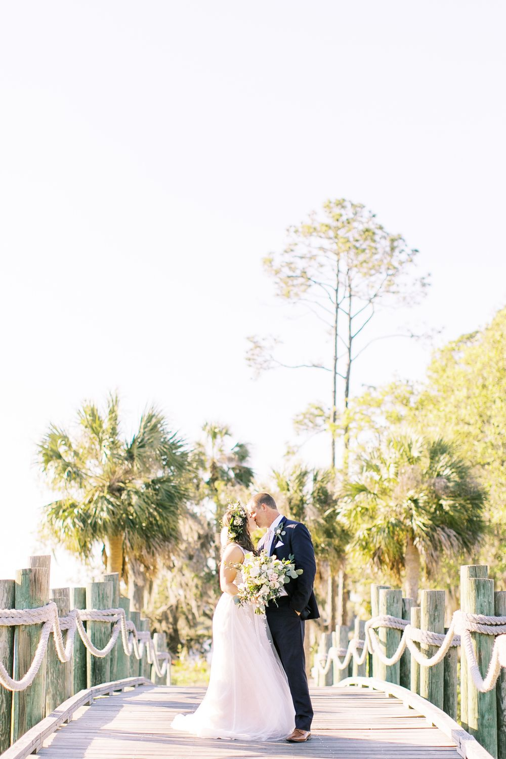 bride and groom share a kiss on top of a bridge in the landings in savannah, ga