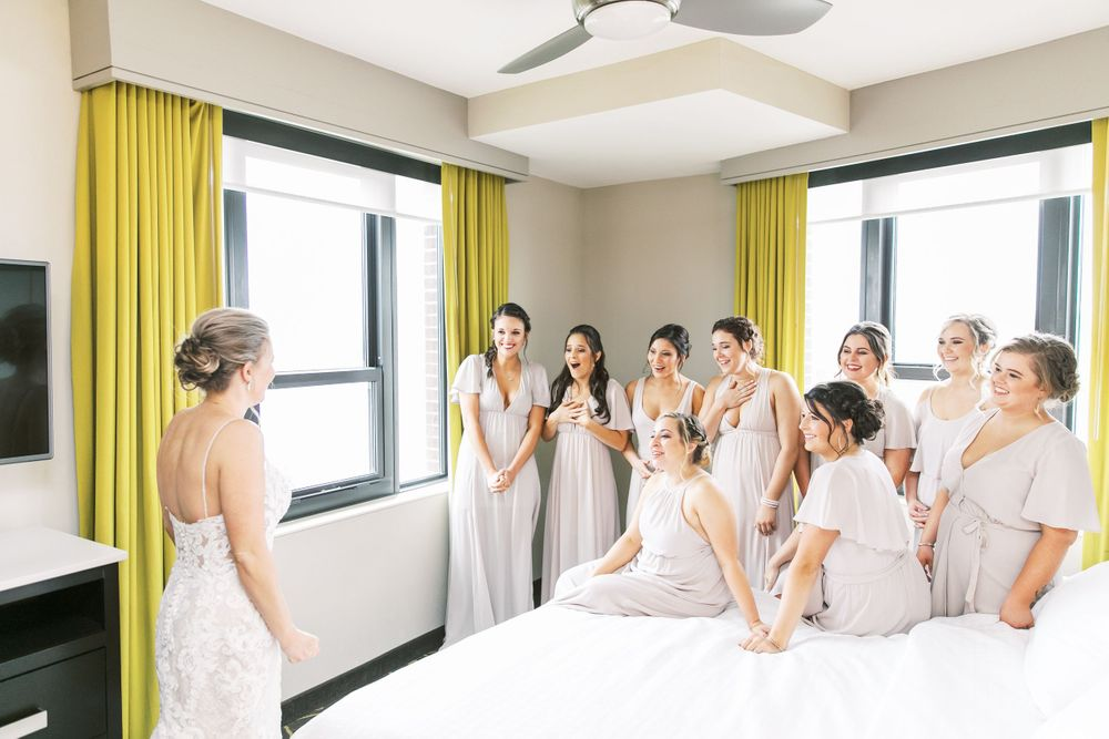 bride does a first look with bridesmaids in the homewood suites in downtown savannah, ga