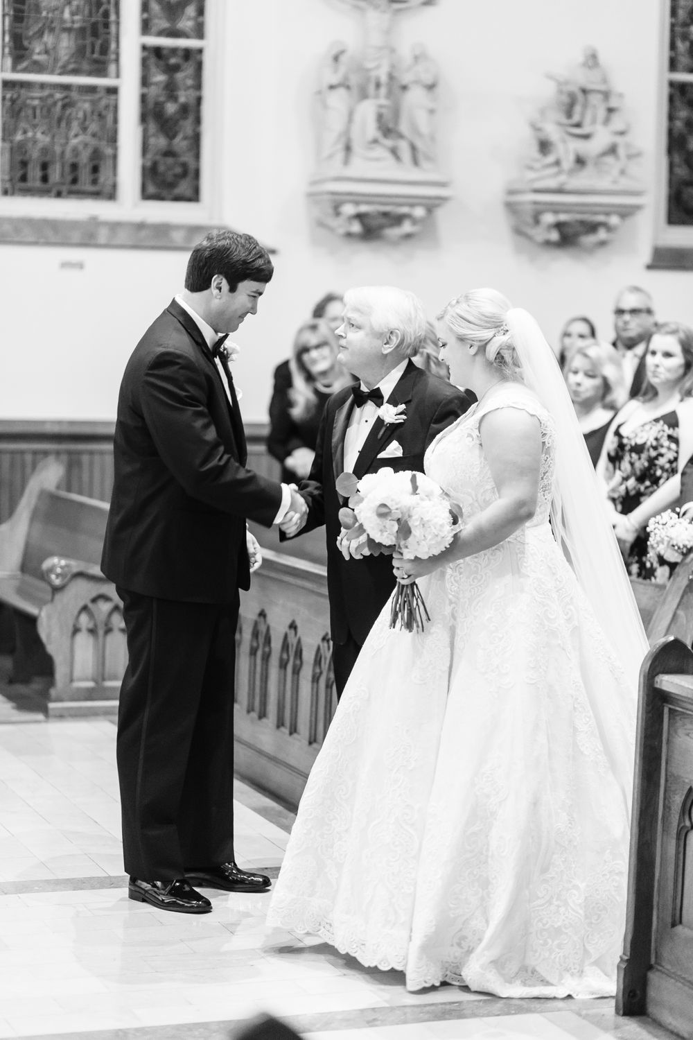father of the bride gives bride away during mass at sacred heart in downtown savannah, ga
