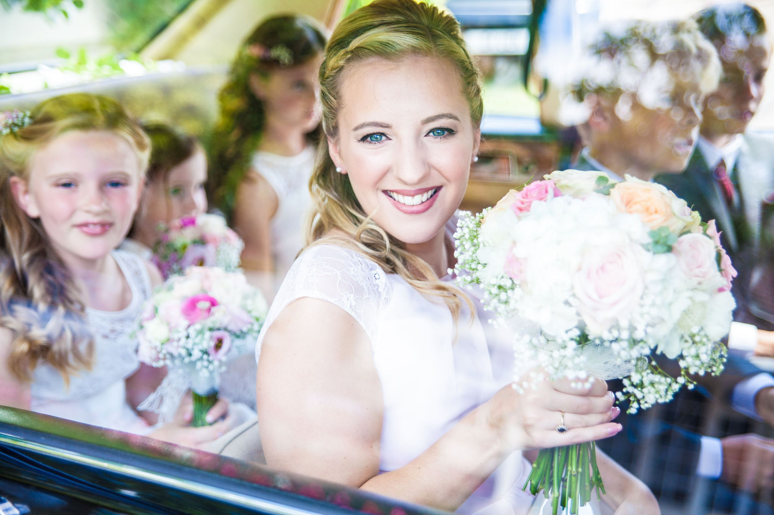 Bridesmaid in car holding bouquet