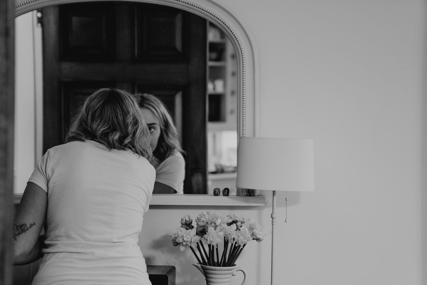 Black and white photo of a bridesmaid doing her make up in a large mirror.