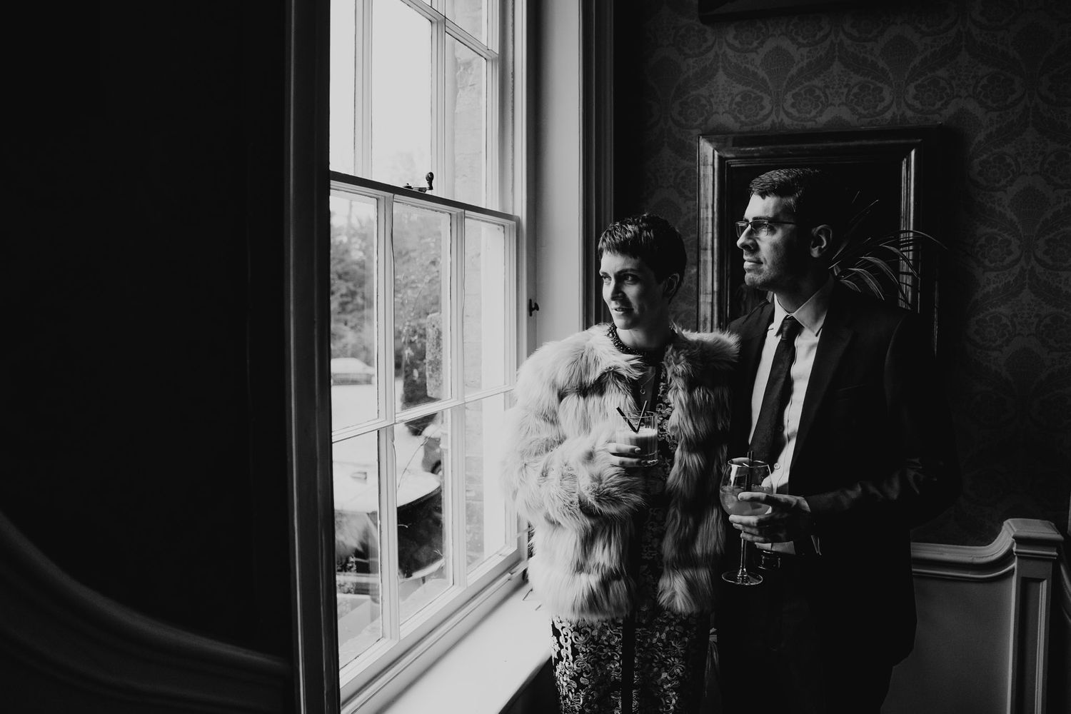 Black and white photo of bride and groom looking out of the window at 10 Castle Street, Dorset