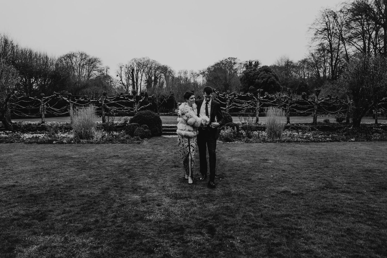 black and white photo of bride and groom walking across the lawns at 10 Castle Street, Dorset.