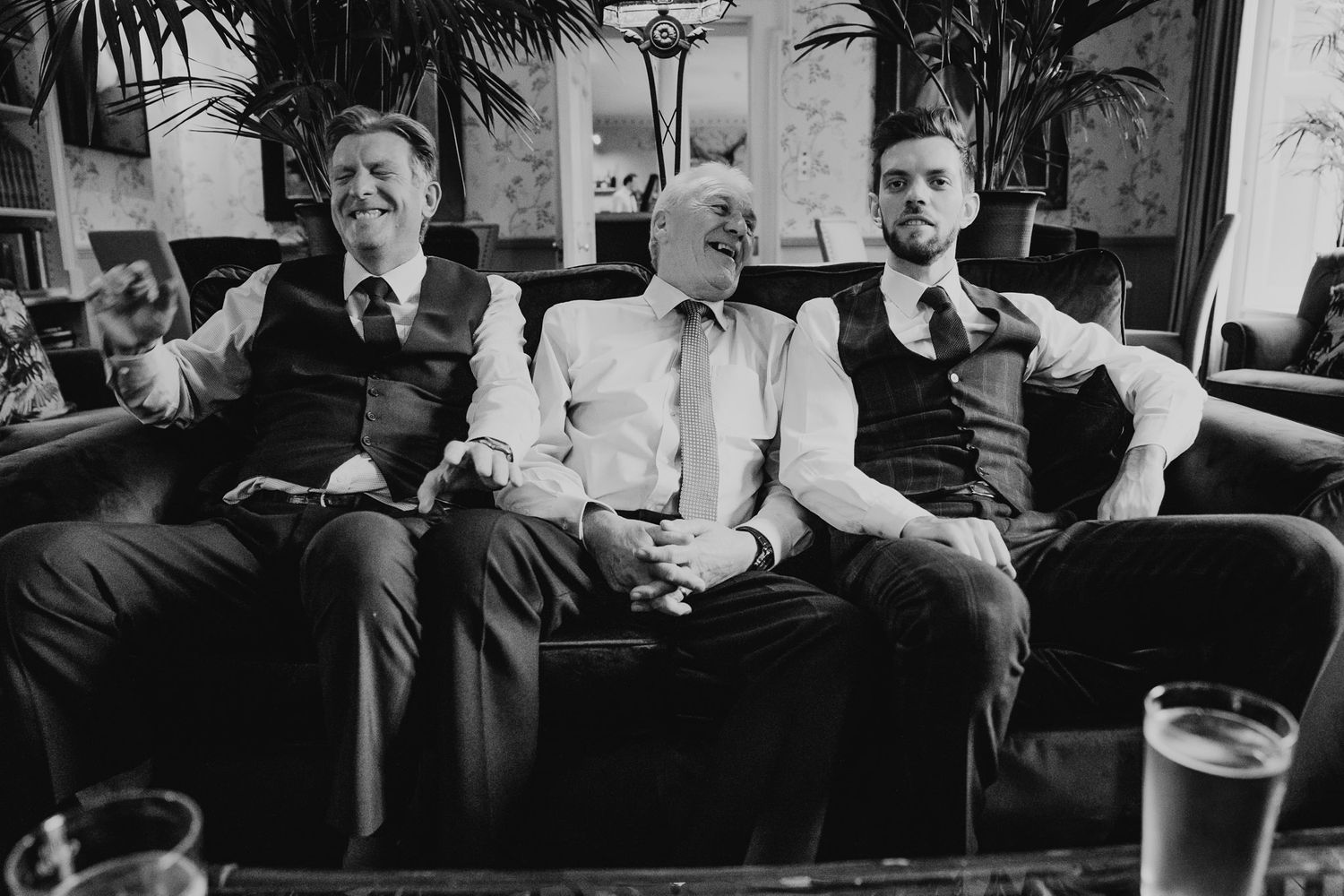 Black and white photo of three men sat laughing on a sofa at a Dorset wedding.