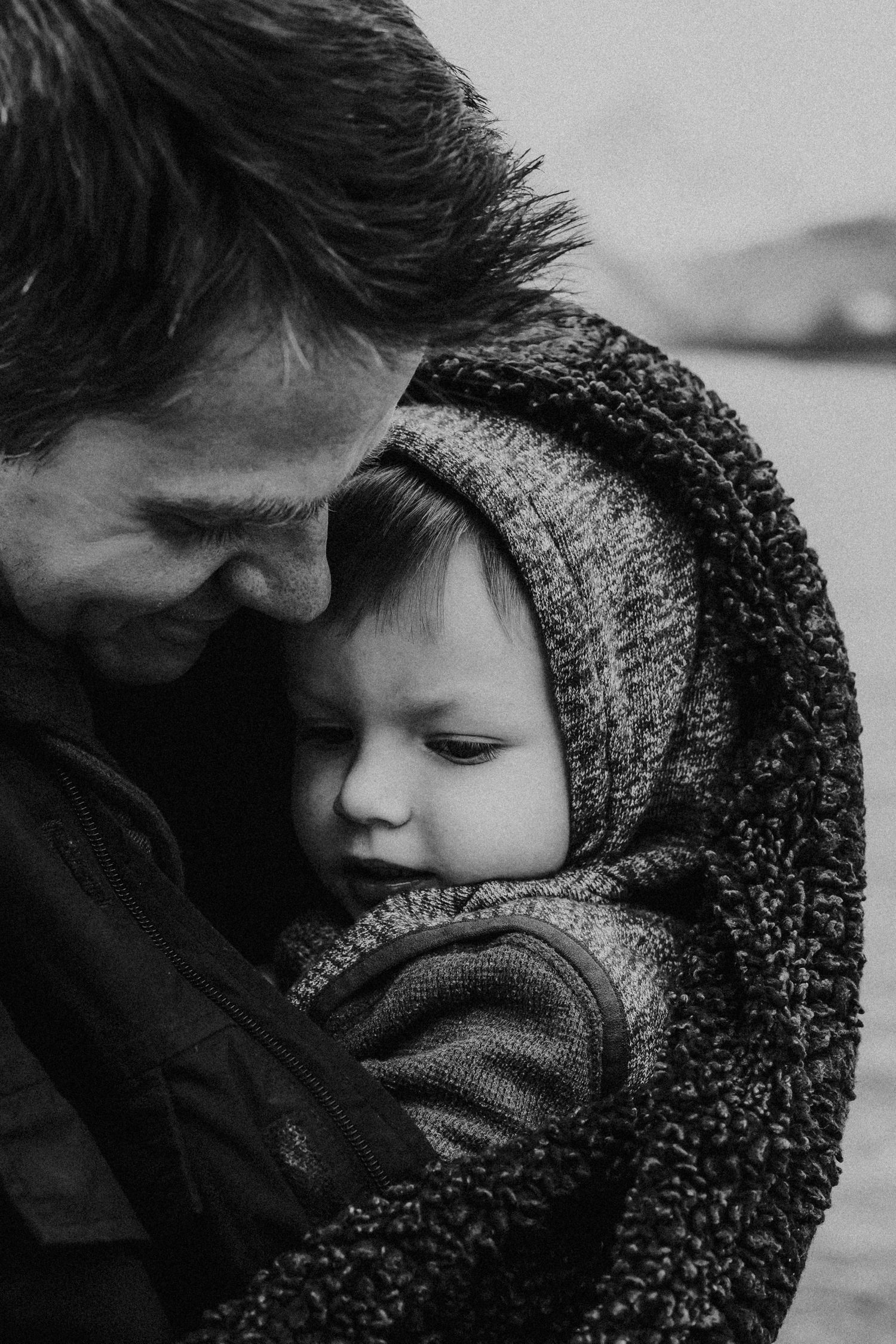 dad holds son in blanket to keep him warm