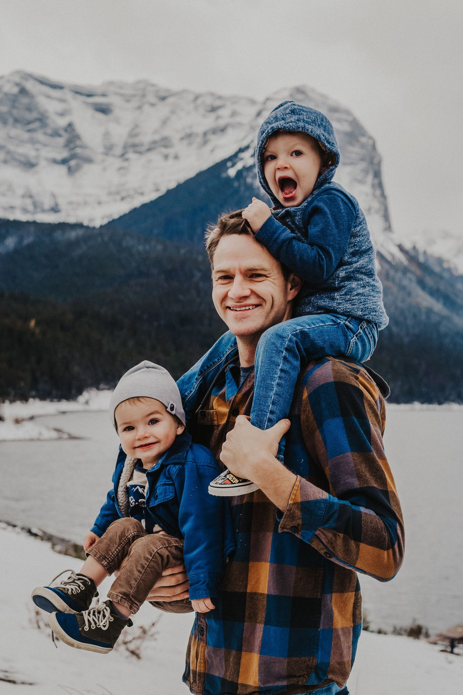 dad holds baby boy and has other son on his shoulders in front of mountains