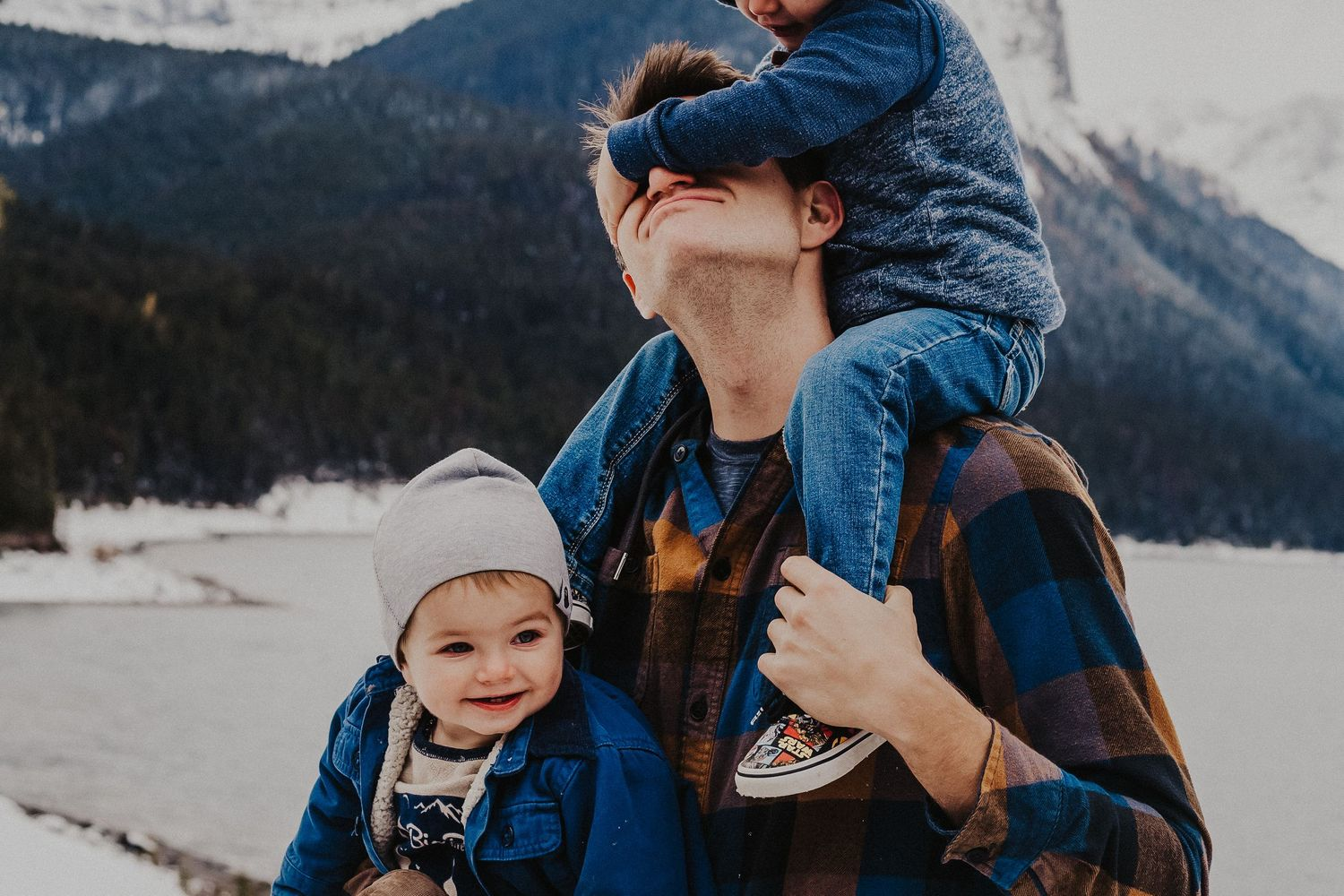 son on dad's shoulders covers his dad's eyes