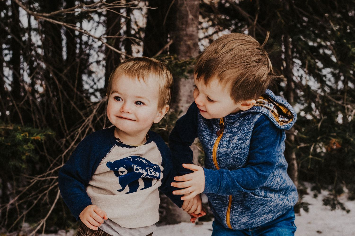 big brother lovingly holds younger brother in the forest