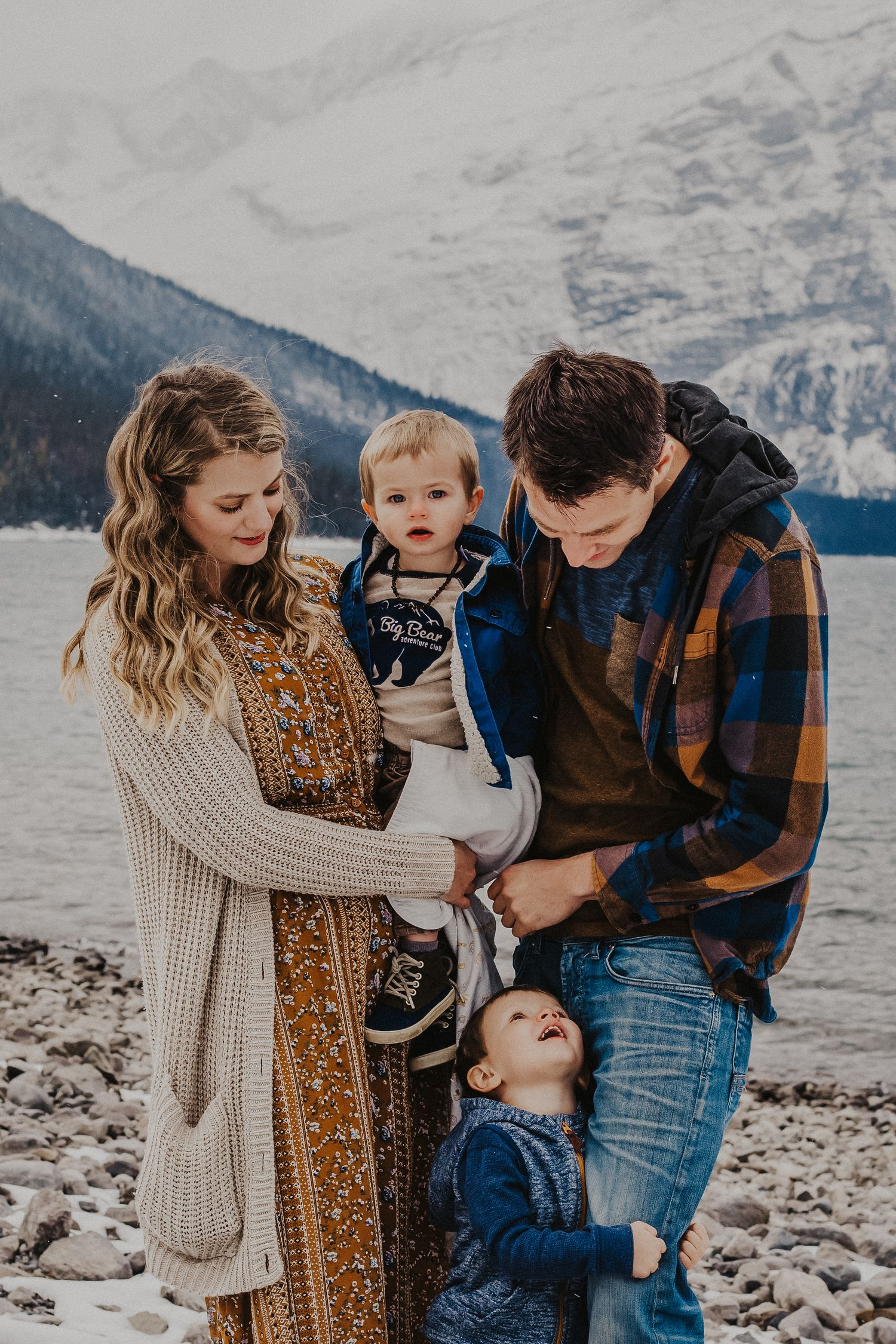 family of four stands in front of mountains smiling