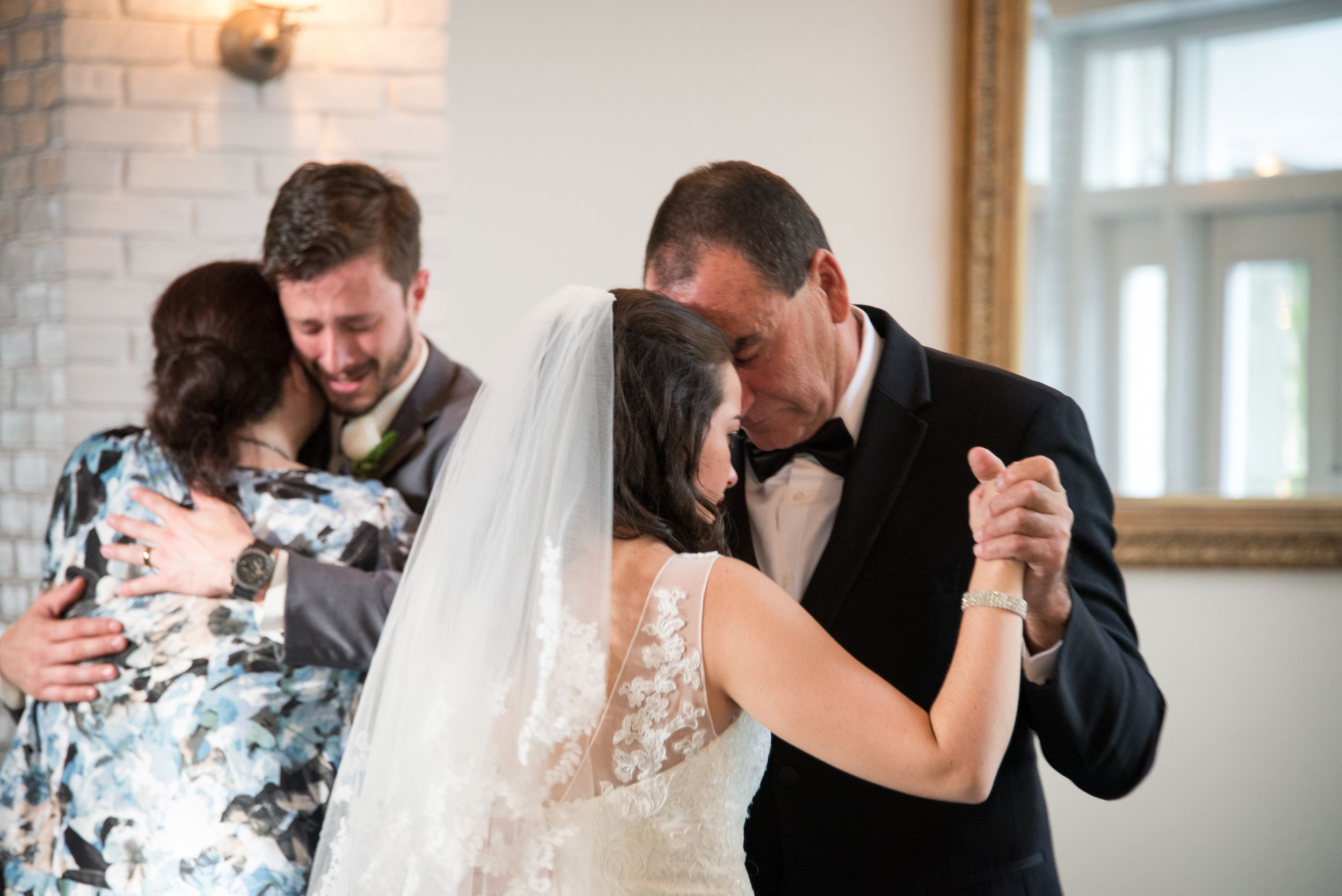 A crying bride dances with her father and a crying groom dances with his mother during a father daughter dance.