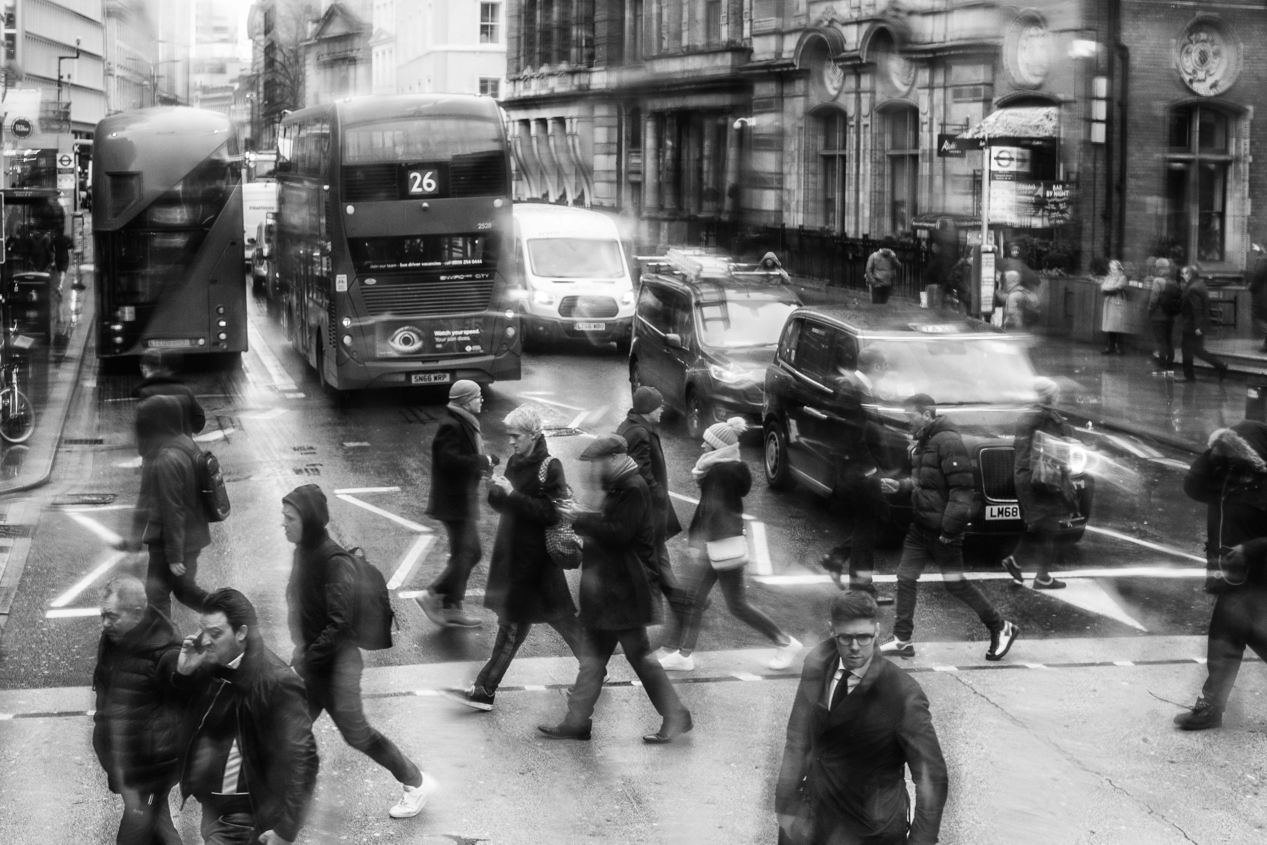 Black and white image of people crossing the street in London
