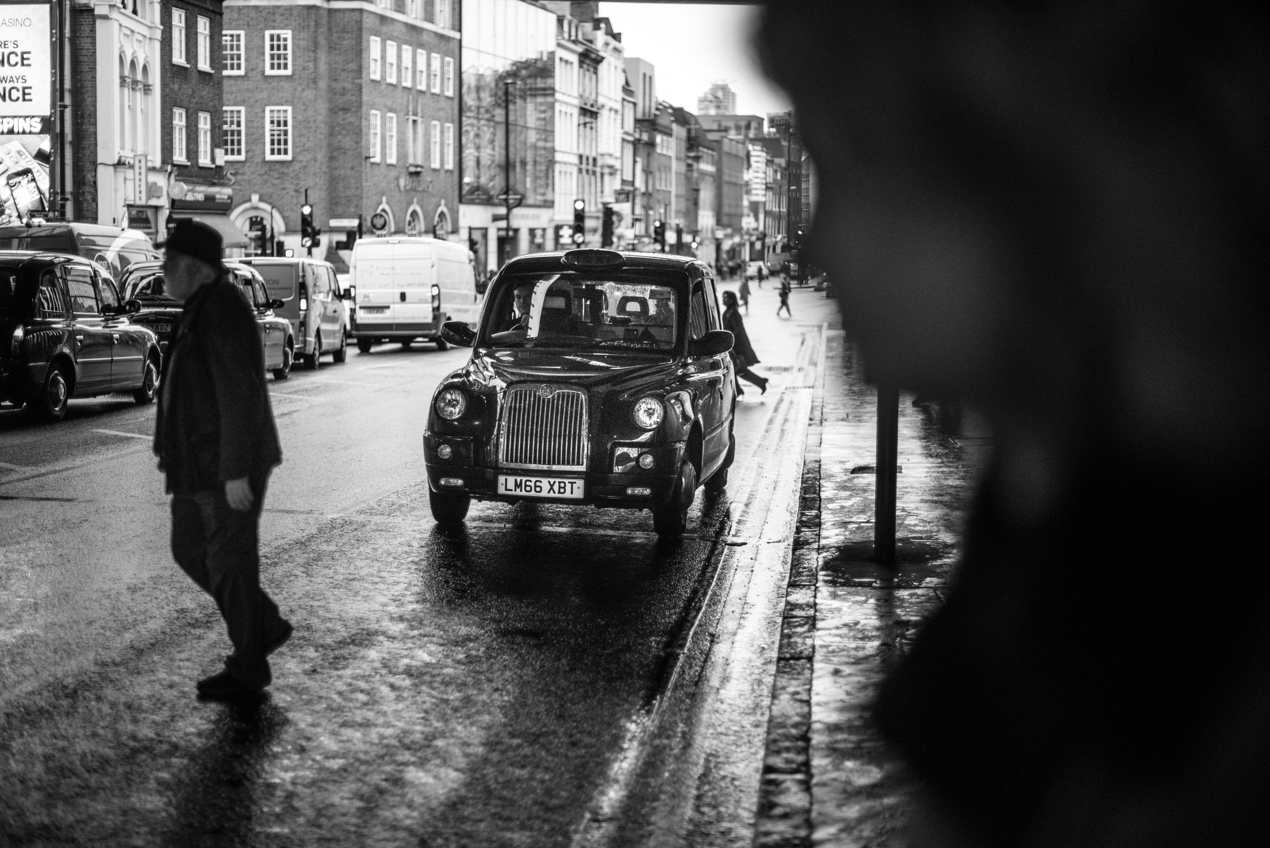 b&w street image in London of people crossing the street in front of a taxi