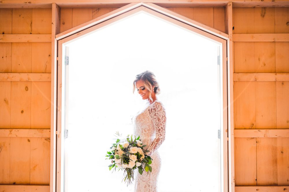 bride smiling at her flowers in between barn doors at Edel Haus alpaca farm