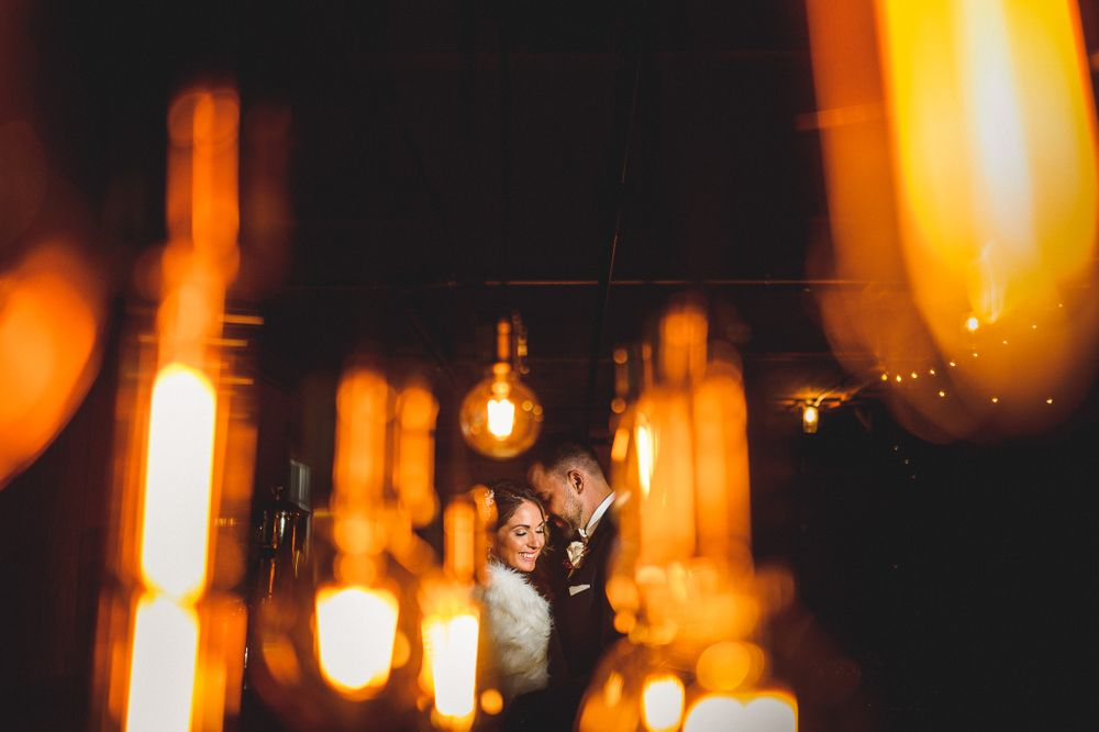 married couple hugging between light string at perona farms