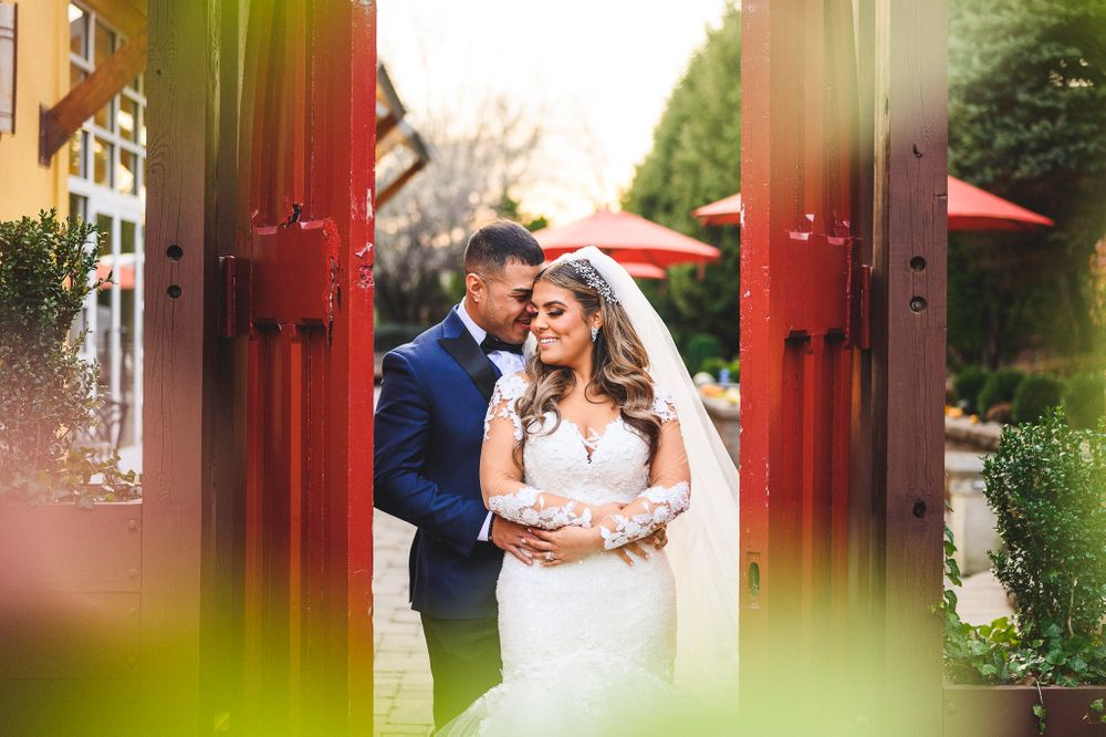 married couple holding each other and smiling between red doors are stone house at stirling ridge