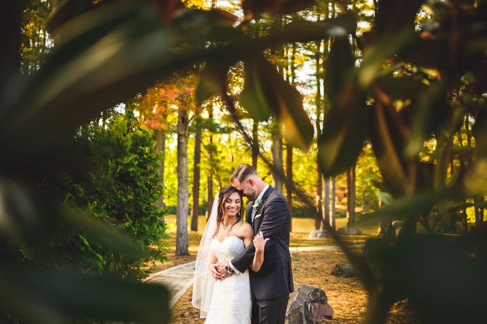 married couple holding each other through trees at The Estate at Farrington Lake