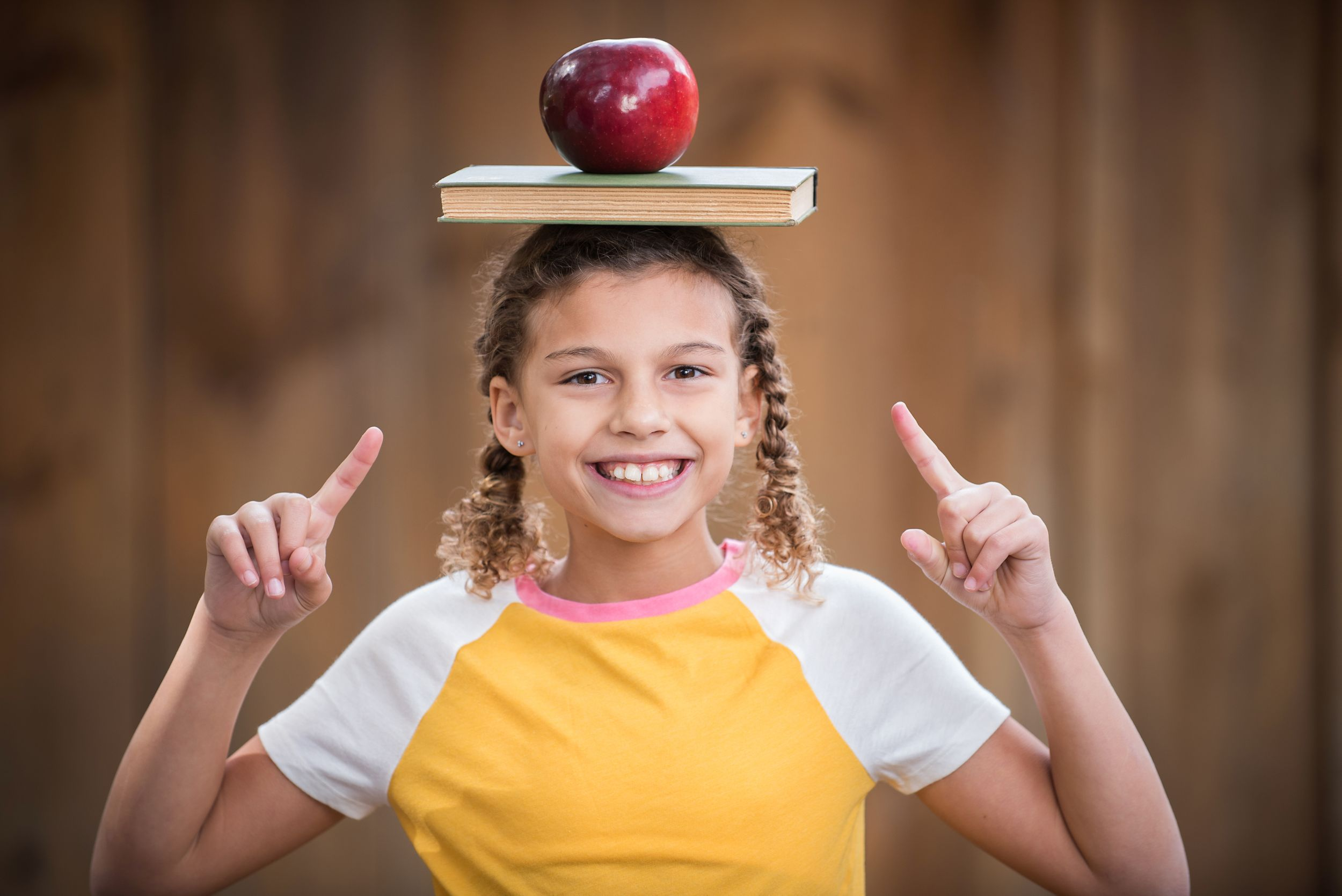 Tween girl back to school look with books and apple balanced on head