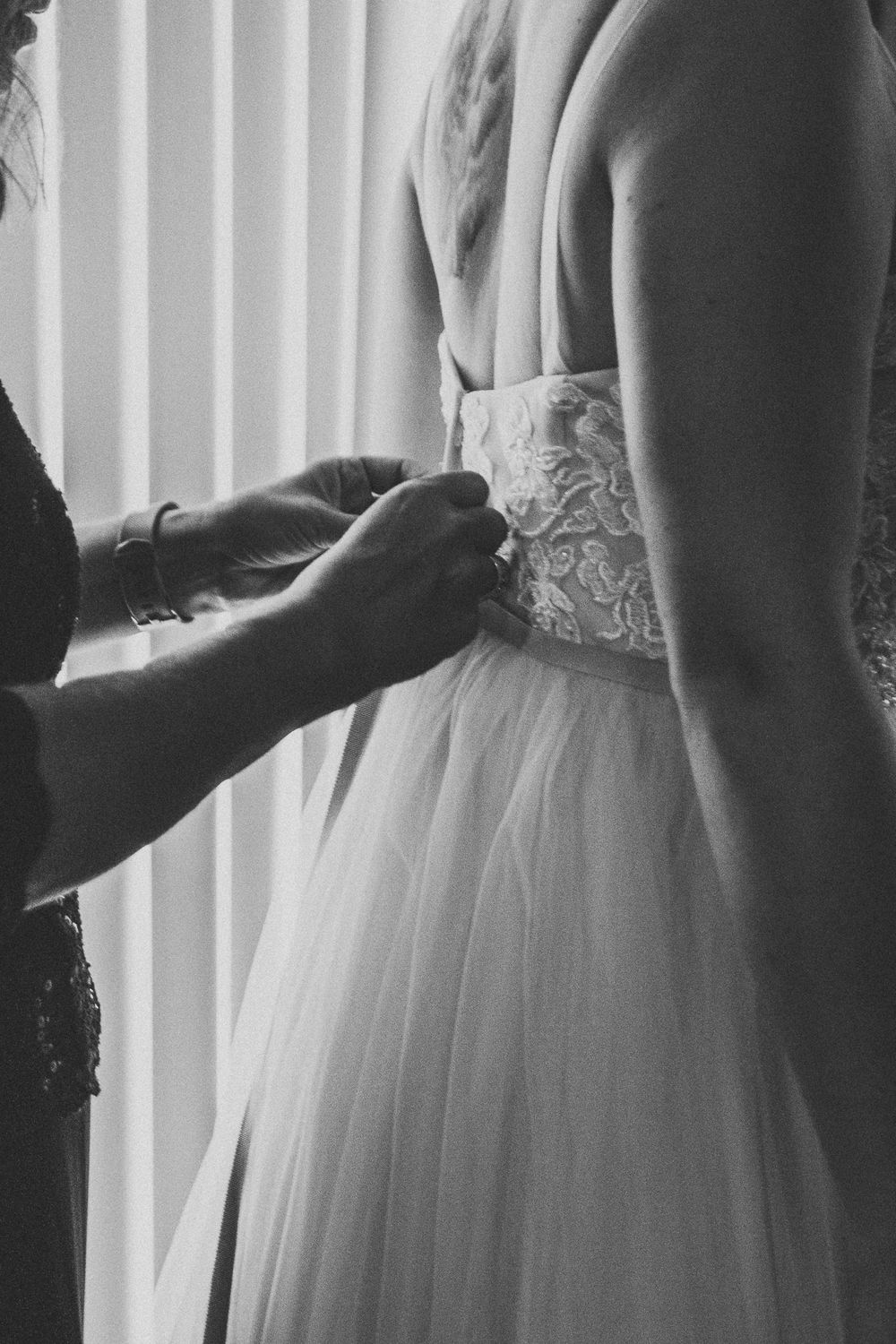 mother of the bride helping her put on her dress