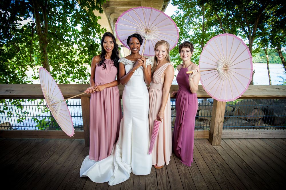 Bride & bridesmaids pose with a parasol under the Gervais Street Bridge wedding at Stone River in West Columbia, SC