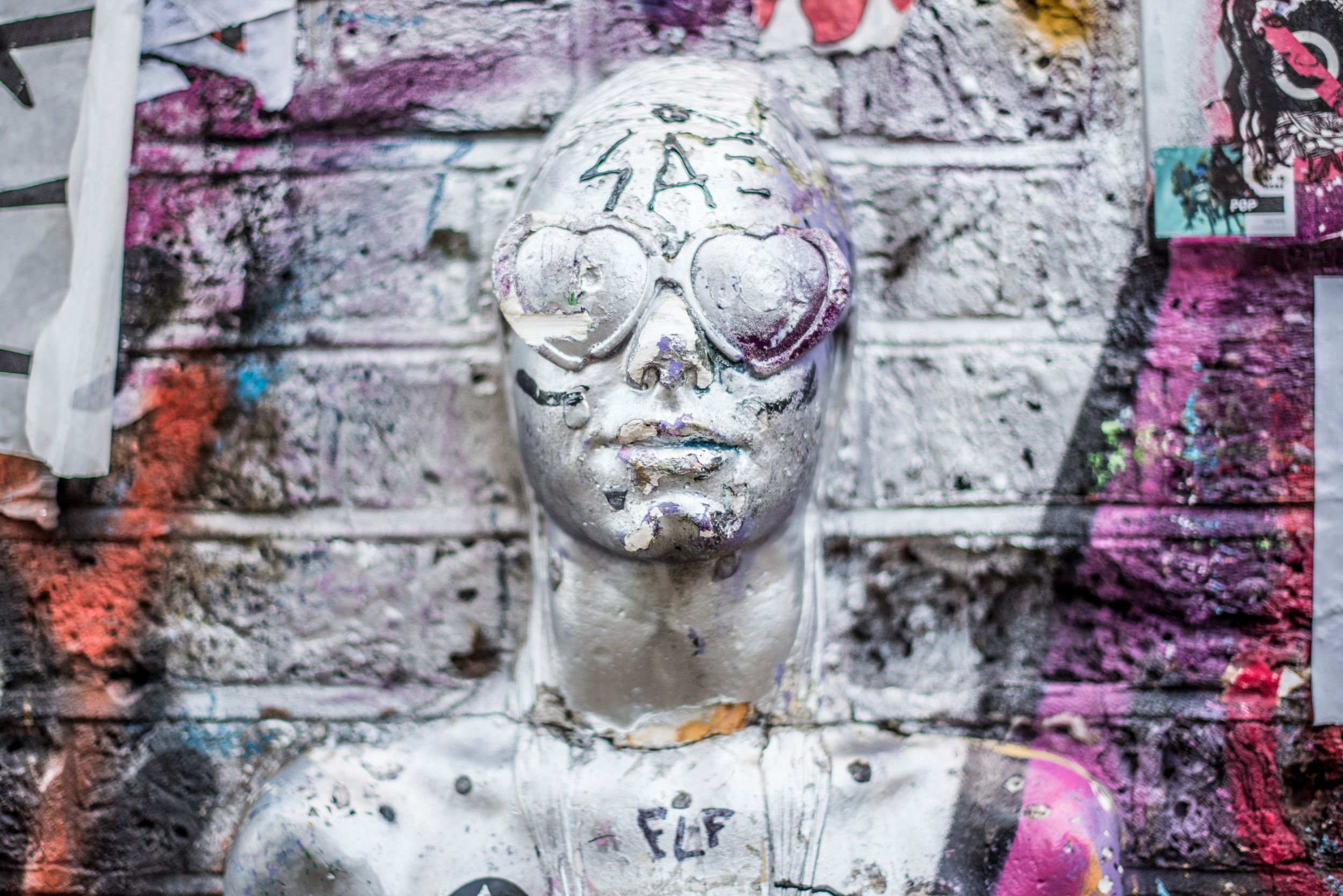 Cool street art of a silver statue with heart glasses spray painted silver in London's artsy Shoreditch neighborhood