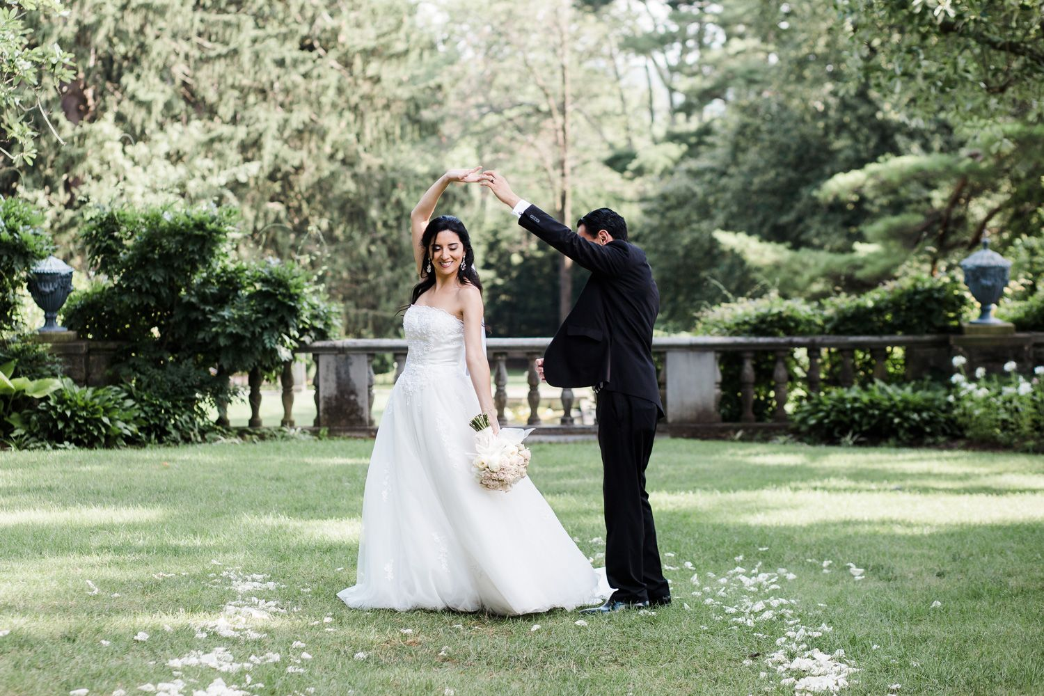 Bride and groom dance with white rose petals on the ground