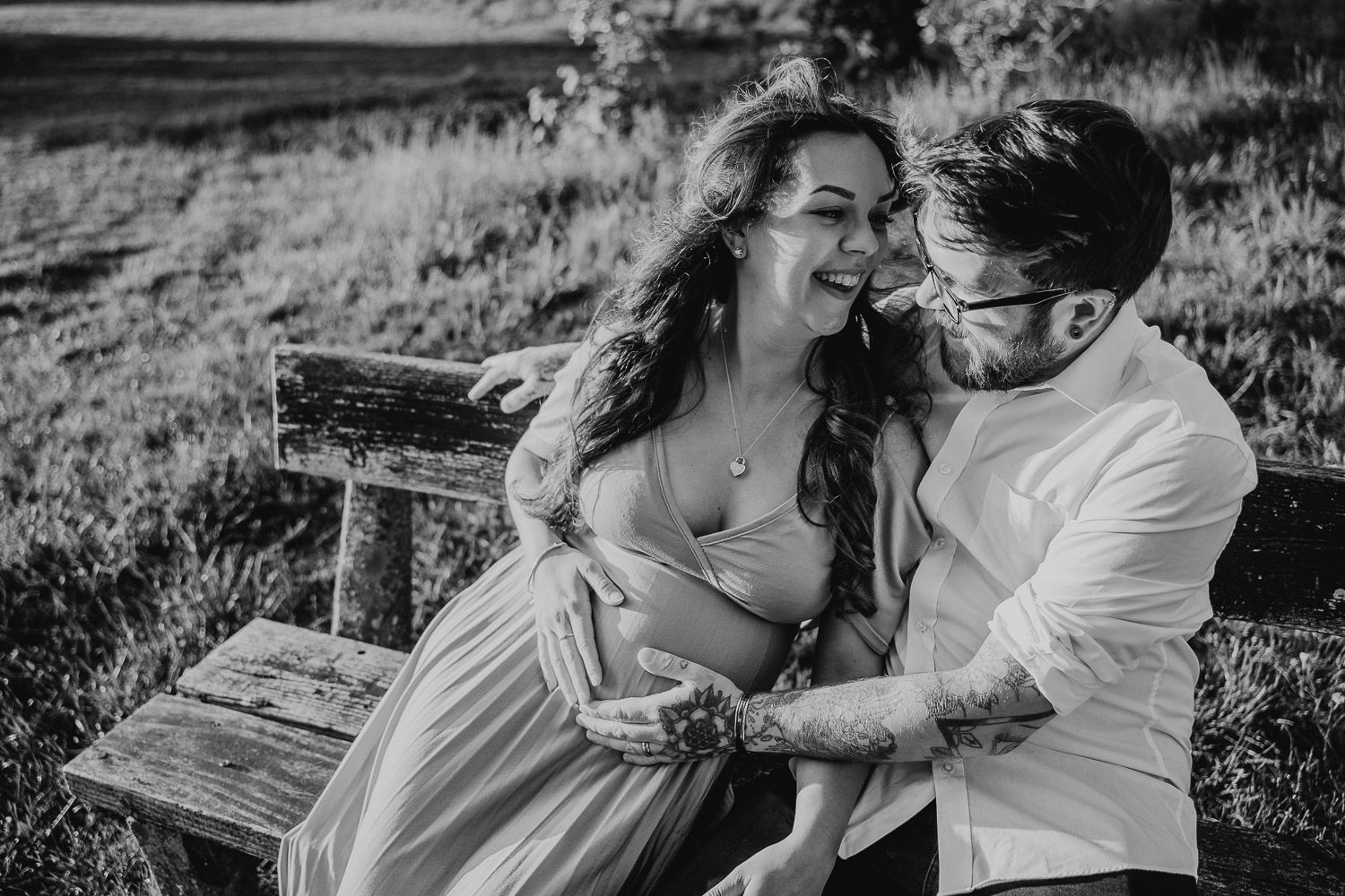 Black and white image of a couple embracing on a bench from a golden hour maternity shoot.