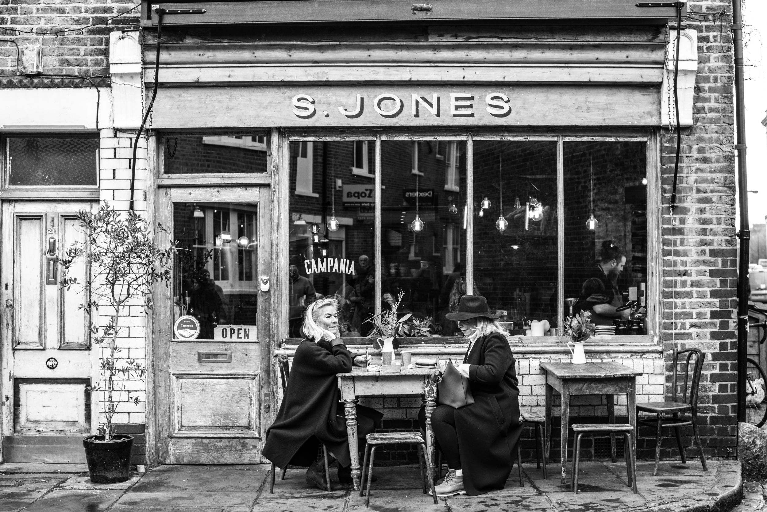 black and white image of two women lunching at an outside table at S. Jones in London's Flower Market area