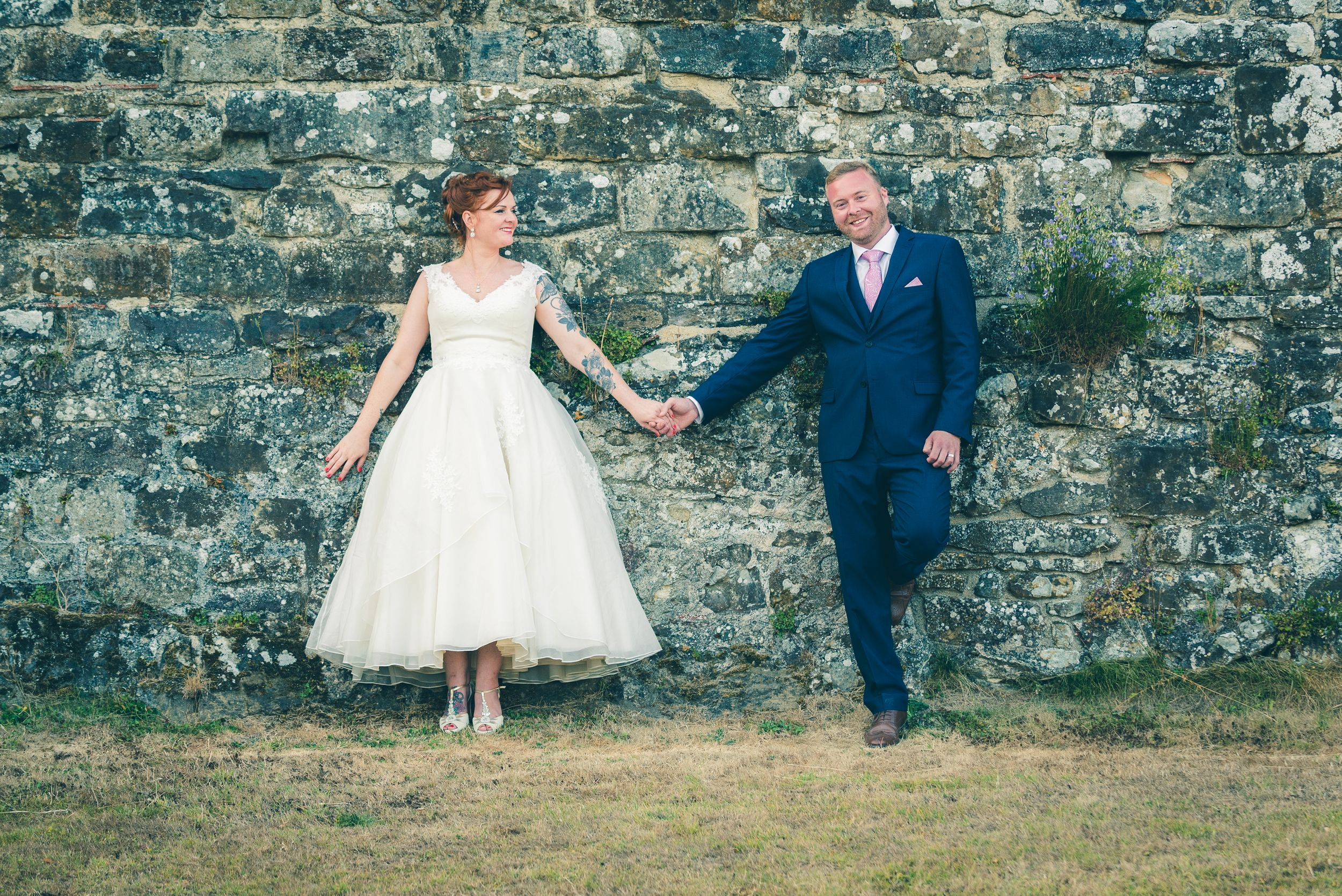 Bride and groom holding hands against a brick wall
