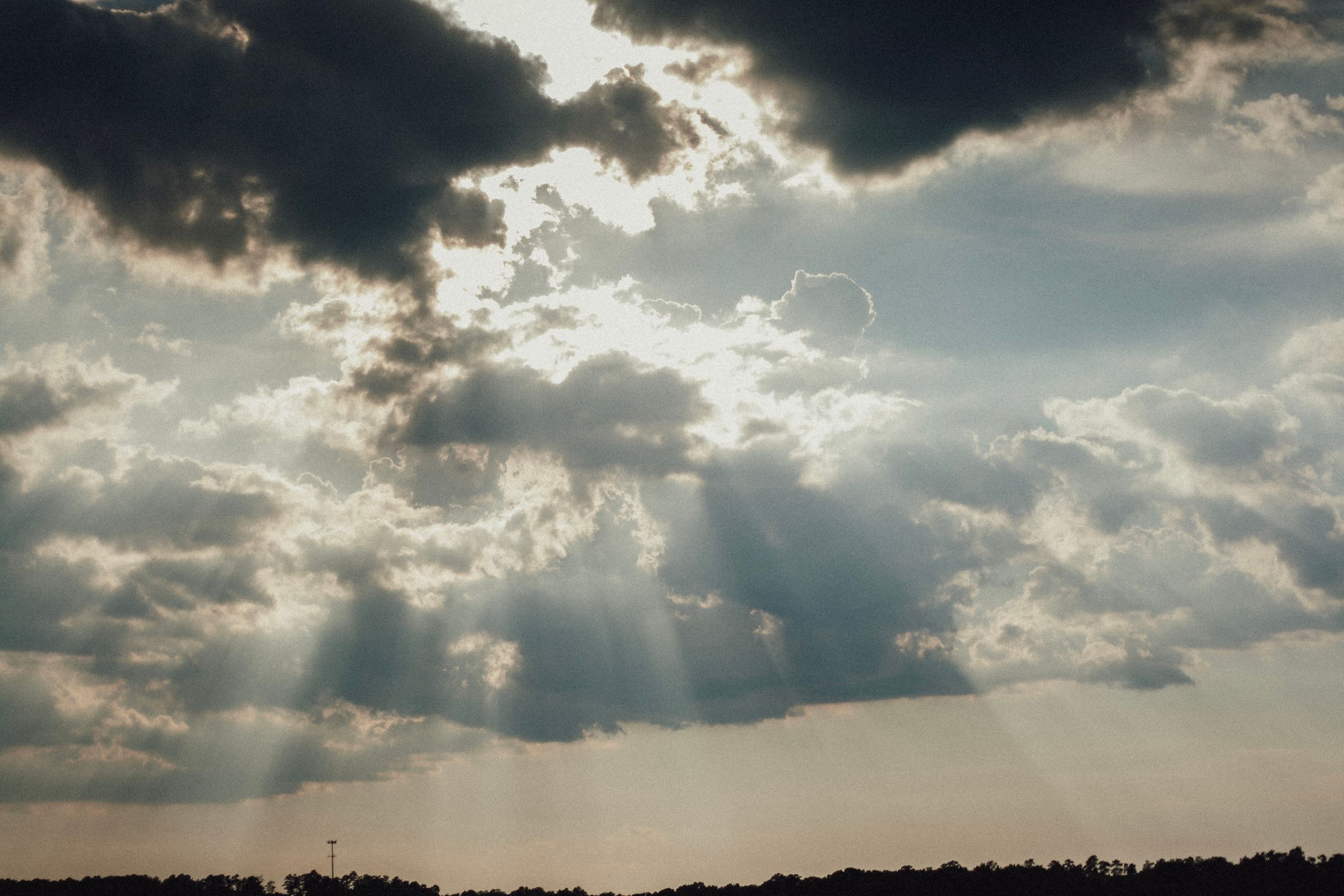 sun shining through the clouds right before sunset at green hills county park in wake forest north carolina