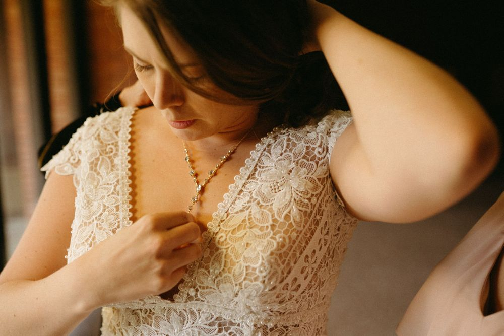 bride-getting-necklace-on-getting-ready-wedding-cowles-library-desmoines-iowa-raelyn-ramey-photography