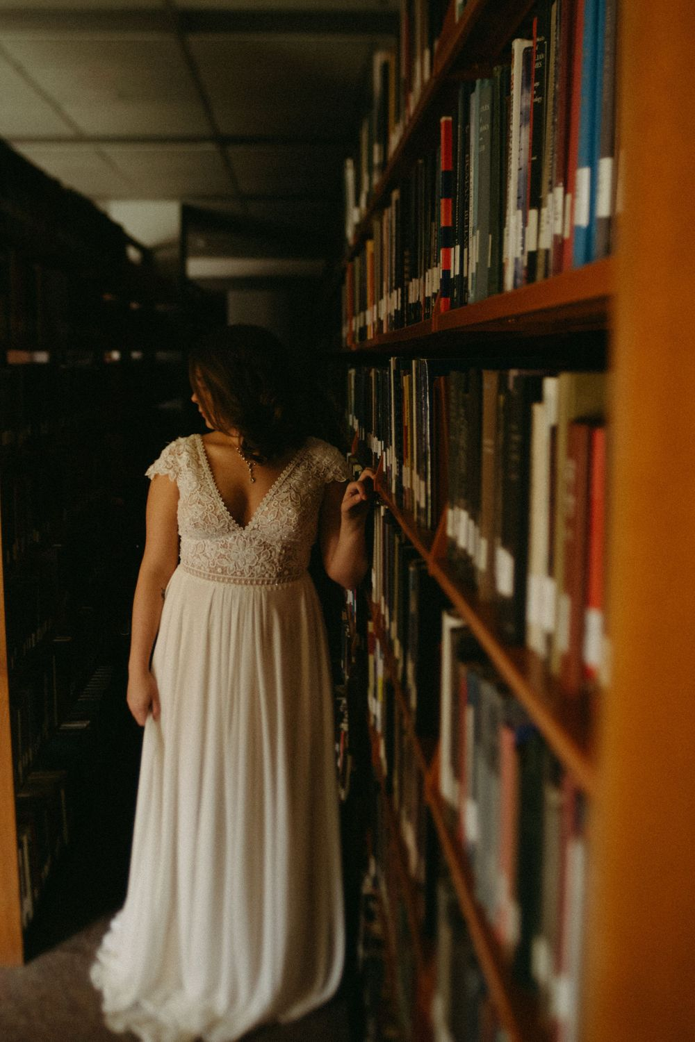 bride-standing-in-book-rows-wedding-cowles-library-desmoines-iowa-raelyn-ramey-photography