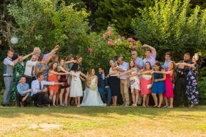 medium sized wedding family photo with guests pointing at the bride and groom, Robert Nelson Wedding Photography