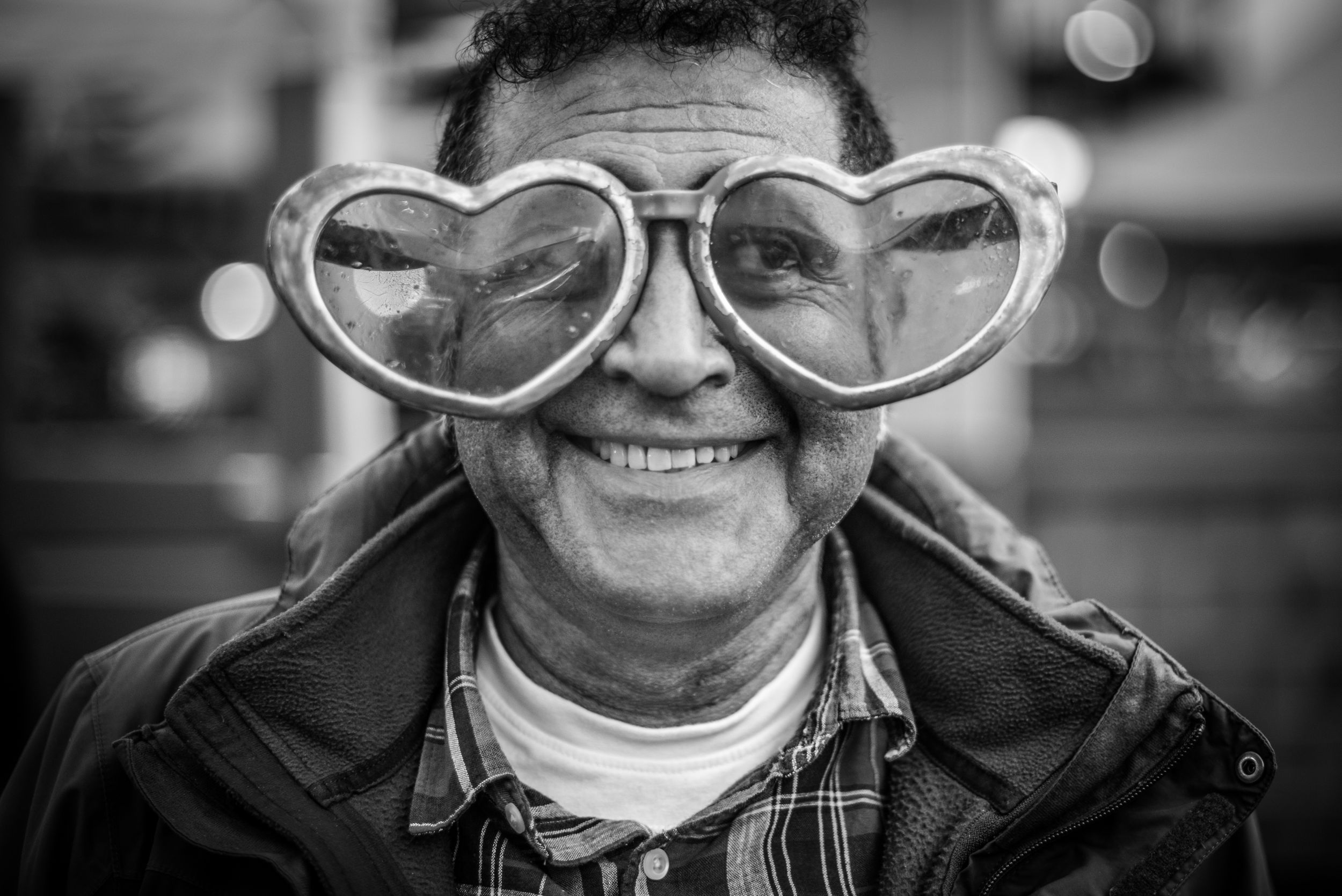 Black & White Portrait of a Stranger of a man wearing oversized heart shaped sunglasses with a slight smile on his face.