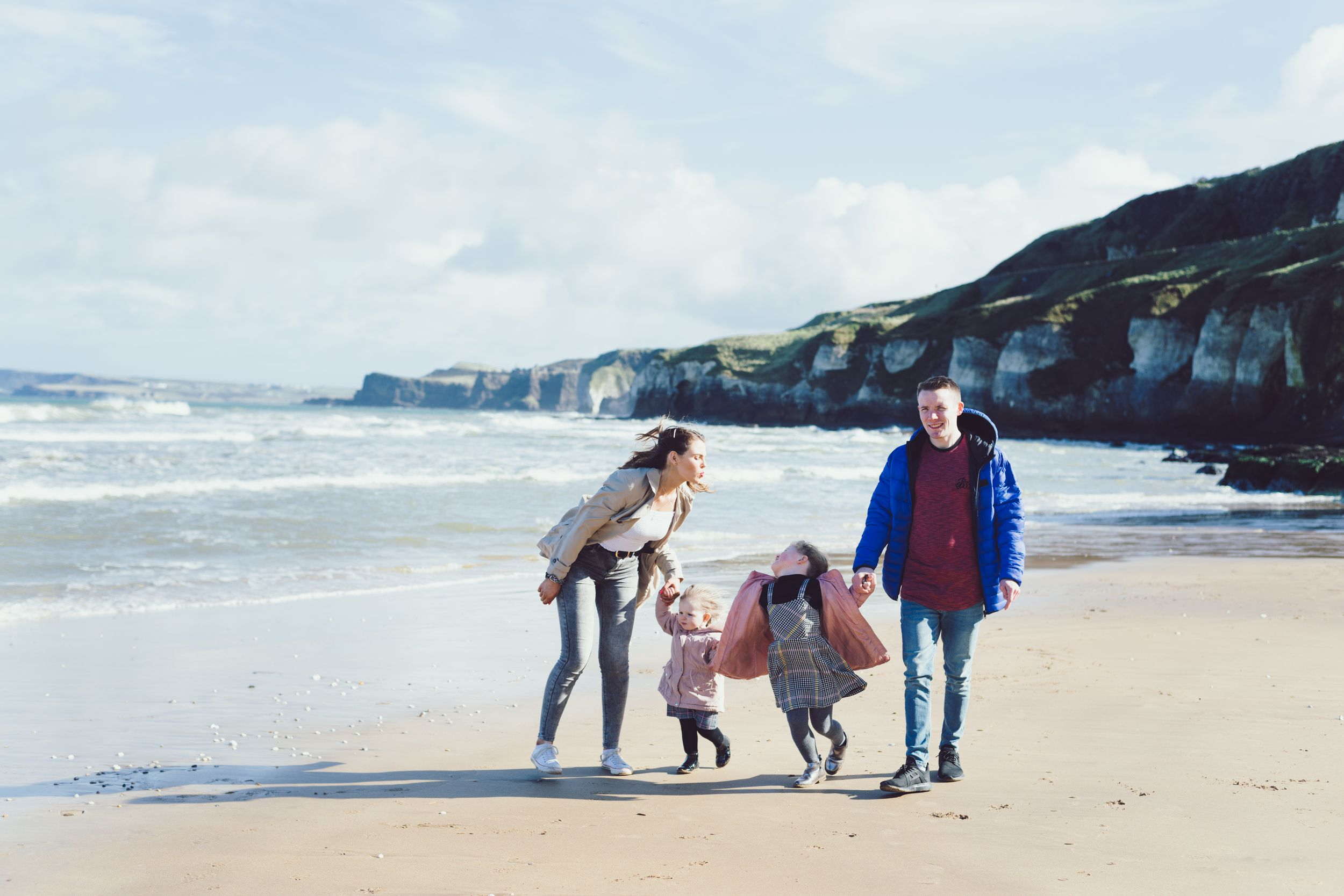 mum, dad and two daughters strolling along the beach at the whiterocks, portrush