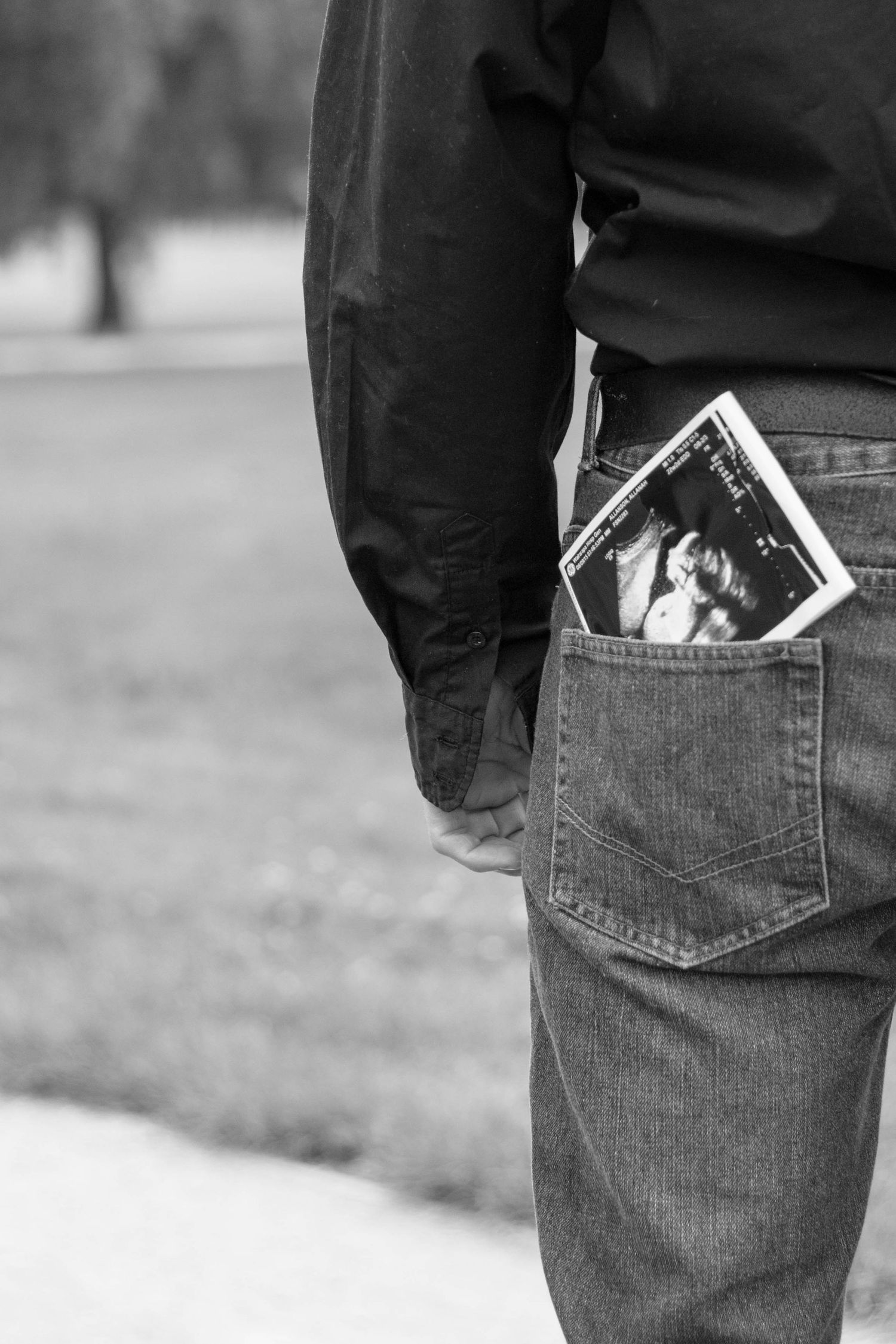 Baby scan in back pocket of father black and white