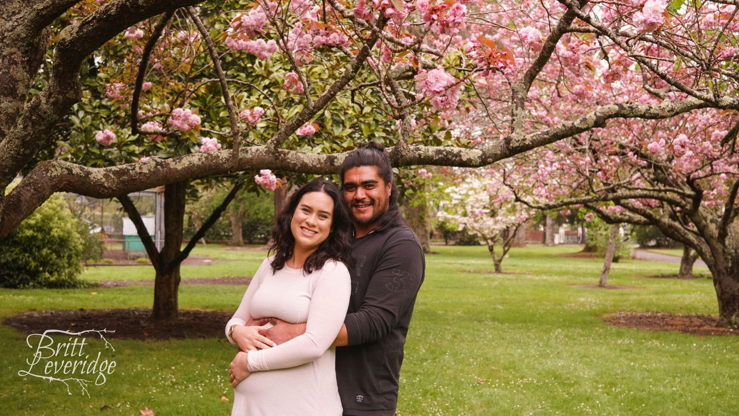 Pregnant lady with partner in front of flowering pink tree