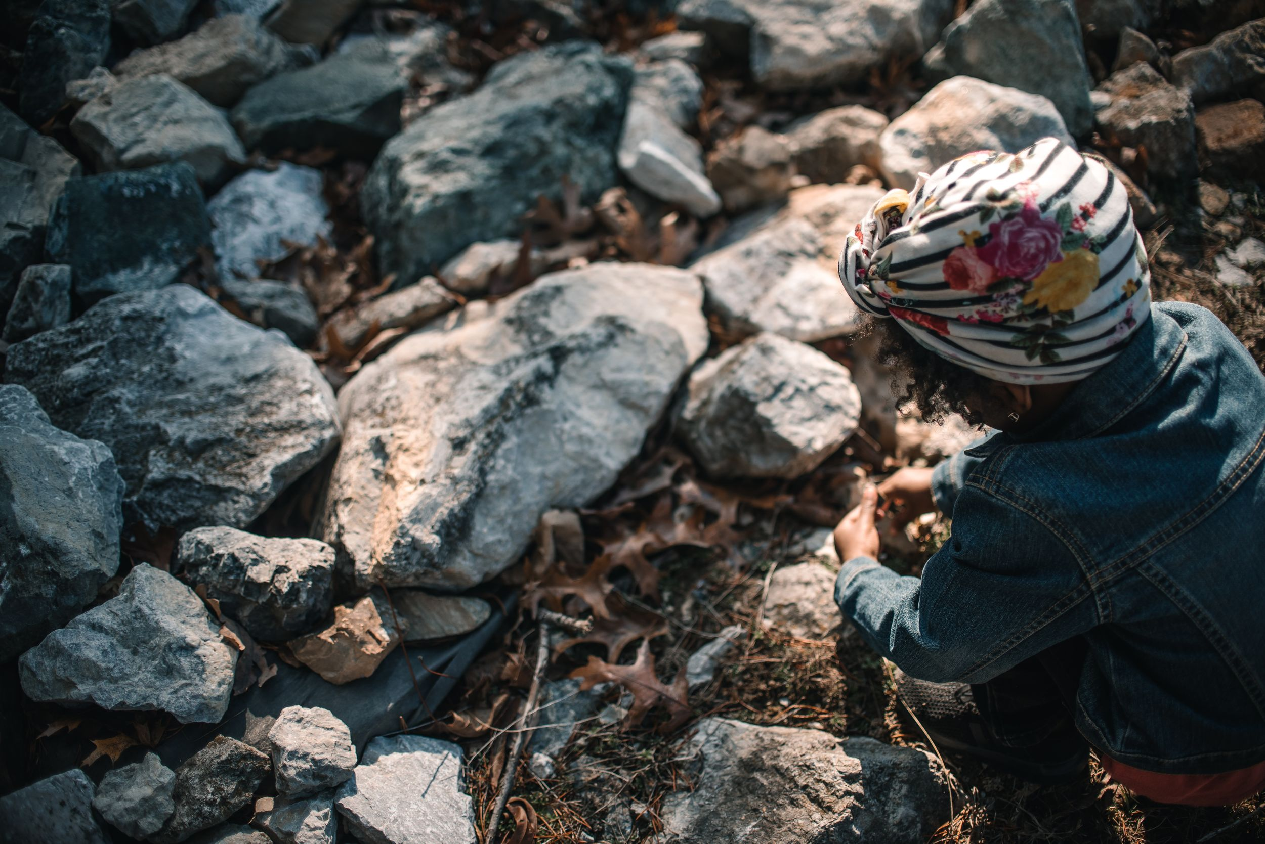 little-girl-with-headwrap-playing-outside-with-rocks