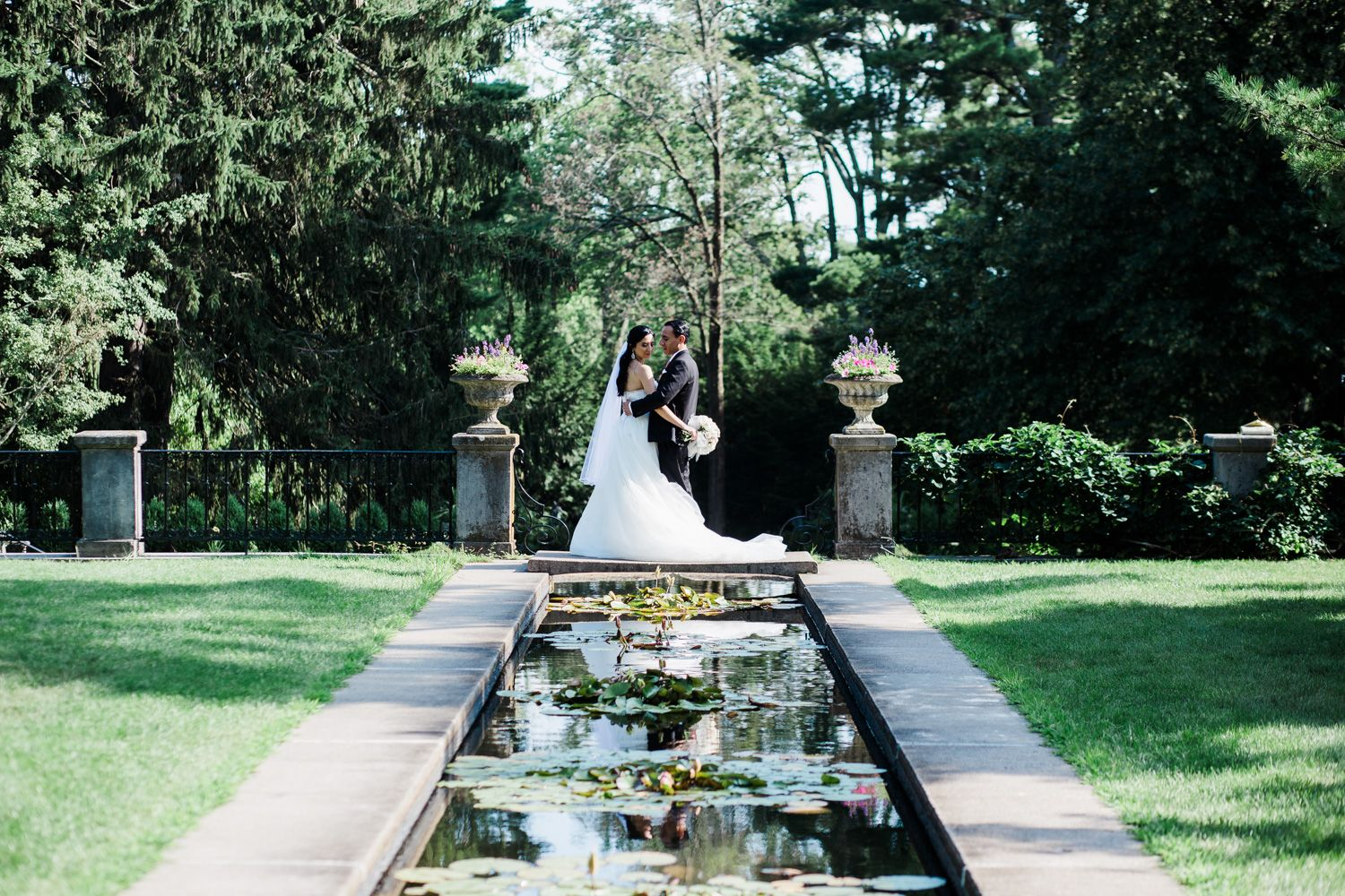 Bride and groom reflected in pool at Skylands Manor
