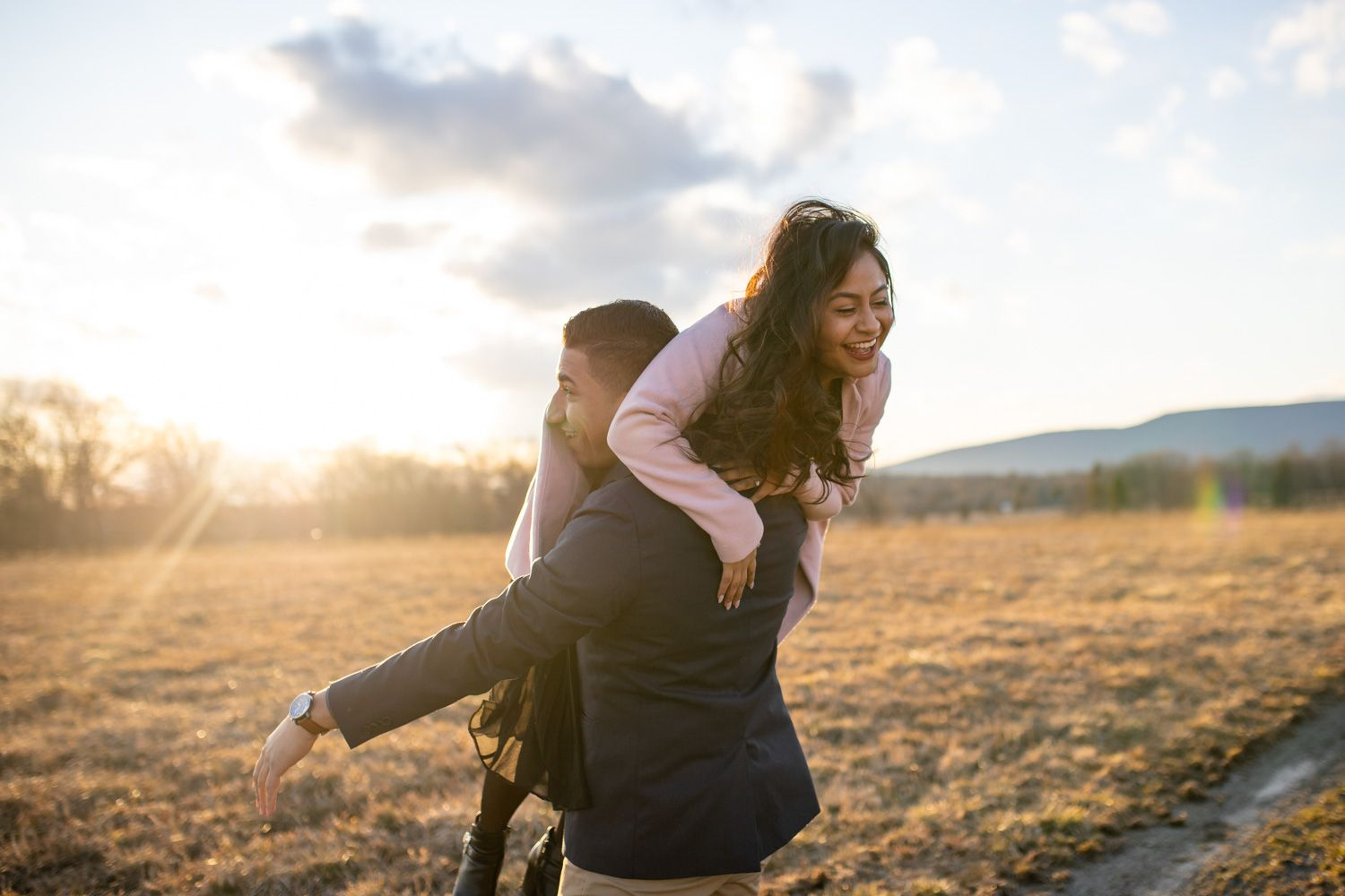 Couple laugh and play during candid adventure engagement session