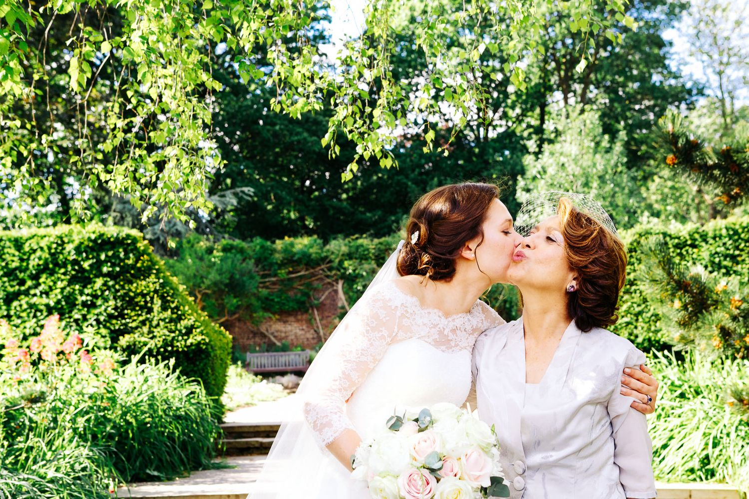 bride giving mother-of-the-bride a kiss at London wedding by destination wedding photographer Elizabeth Armitage