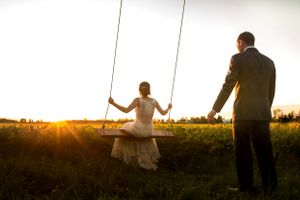 Groom Pushing Bride on Swing